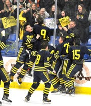 Hartland celebrates its Division 2 state championship after defeating Trenton, 4-0, on Saturday at USA Hockey Arena in Plymouth.