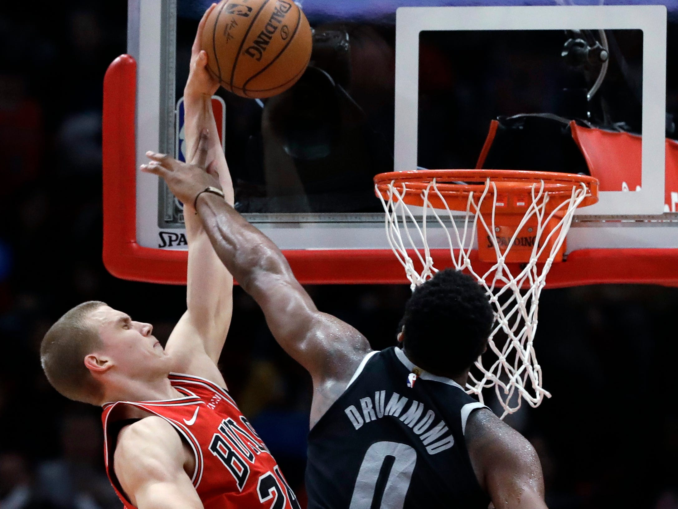 Chicago Bulls forward Lauri Markkanen, left, shoots against Detroit Pistons center Andre Drummond during the first half of an NBA basketball game.
