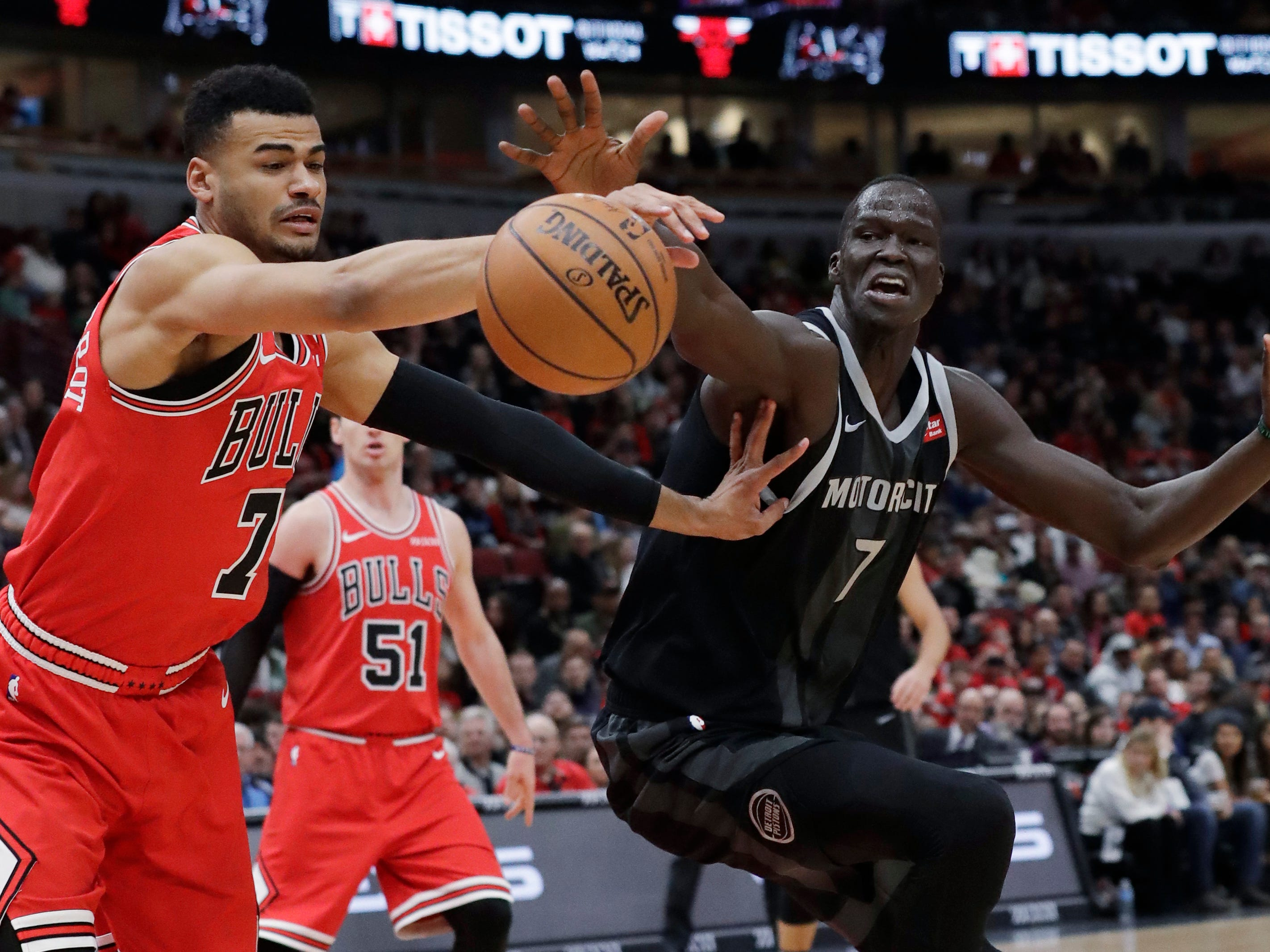 Chicago Bulls guard/forward Timothy Luwawu-Cabarrot, left, and Detroit Pistons forward Thon Maker reach for the ball during the first half of an NBA basketball game Friday, March 8, 2019, in Chicago.