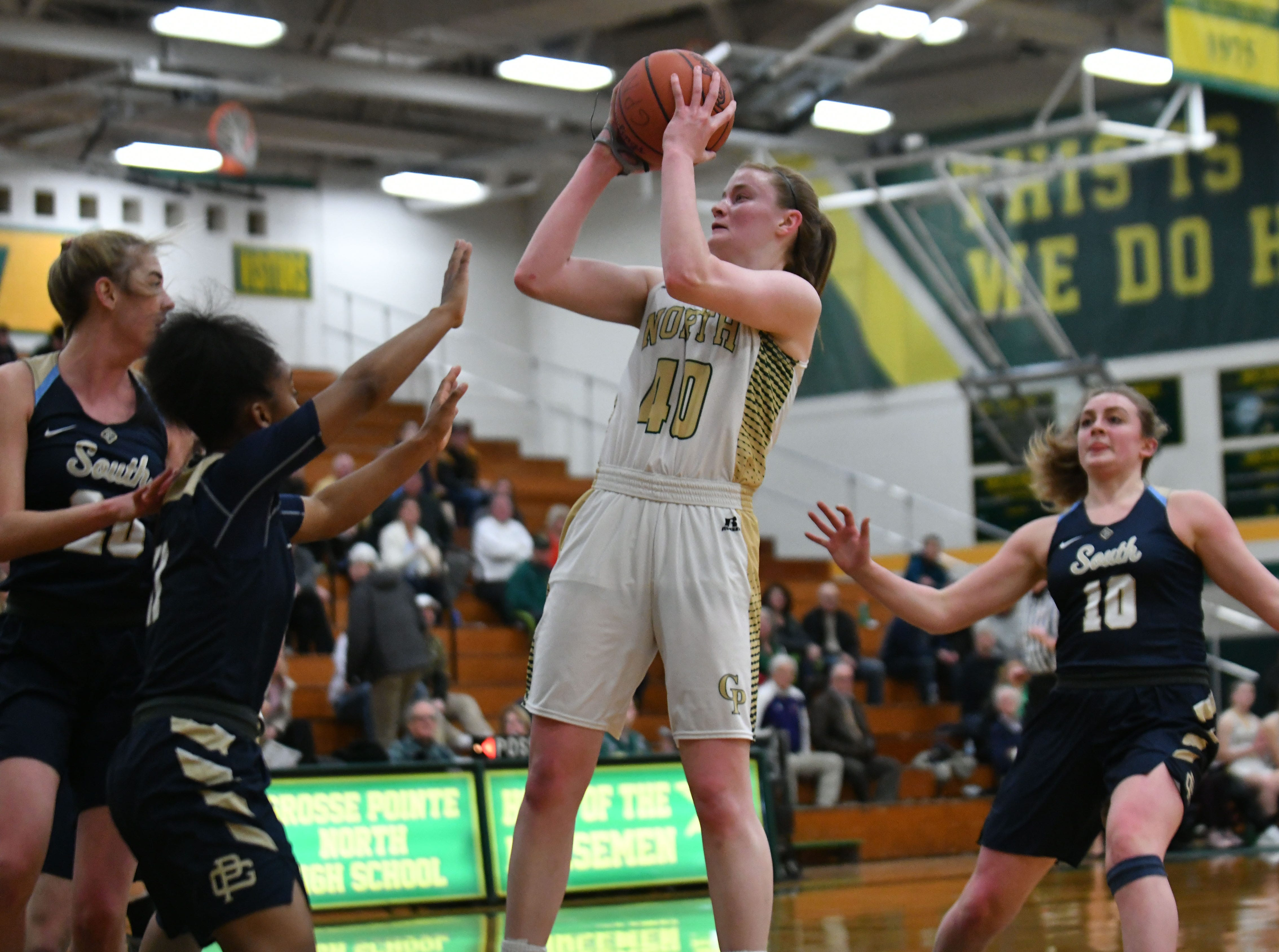 Grosse Pointe North senior Julia Ayrault shoots a jump shot, while surrounded by Grosse Pointe South defenders in the first half.