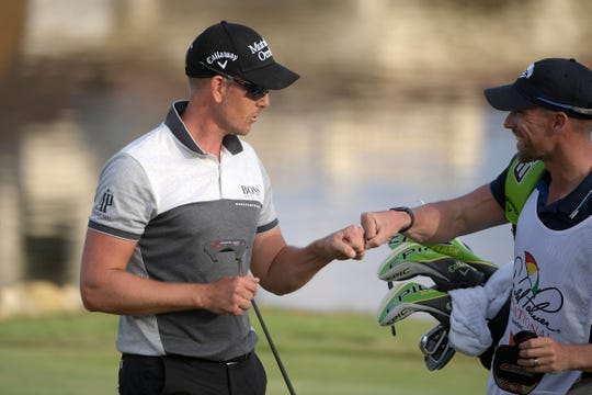 Henrik Stenson, left, gets a fist bump from his caddie after making a putt on the 18th green.