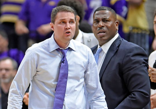LSU head coach Will Wade, left, and assistant coach Tony Benford, right, watch the second half of an NCAA college basketball game in Baton Rouge, La. Benford has been named interim head coach after Wade was suspended amid concerns about the recruiting tactics he used to build his team.