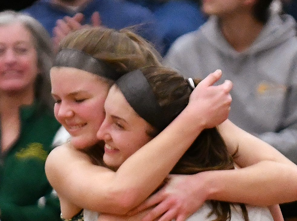 Grosse Pointe North seniors Madeline Mills (left) hugs teammate Evelyn Zacharias after the final buzzer of a 42-23 victory over rival Grosse Pointe South in the district finals at Grosse Pointe North High School on Friday, March 8, 2019.