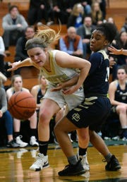 Grosse Pointe North senior Madeline Mills is fouled by Grosse Pointe South's Sydni Hall in the first half.