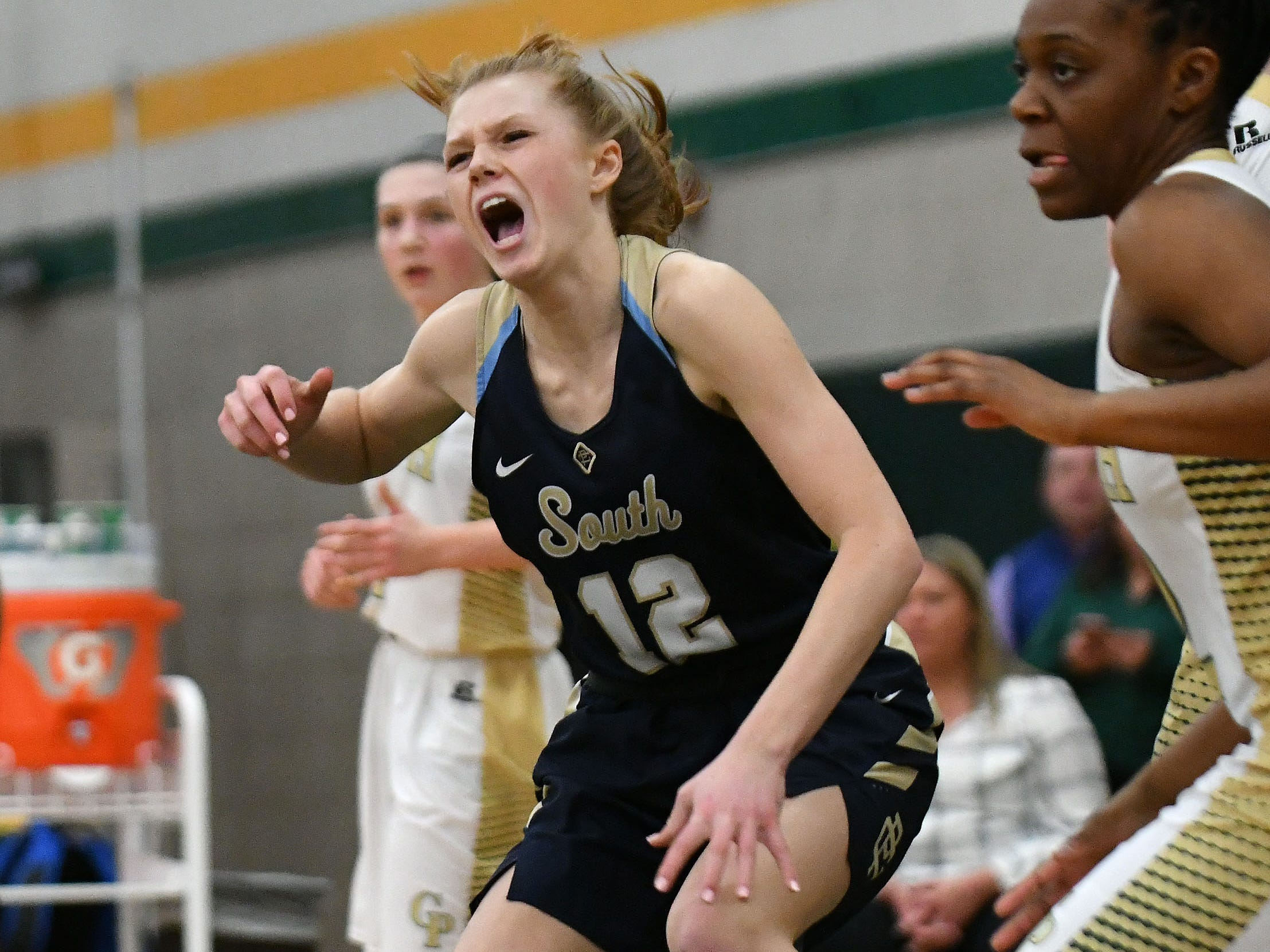 Grosse Pointe South's Keely Conlan grimaces in pain after making a pass. She was injured on the play and had to be helped off the court in the first half.   on Friday, March 8, 2019.