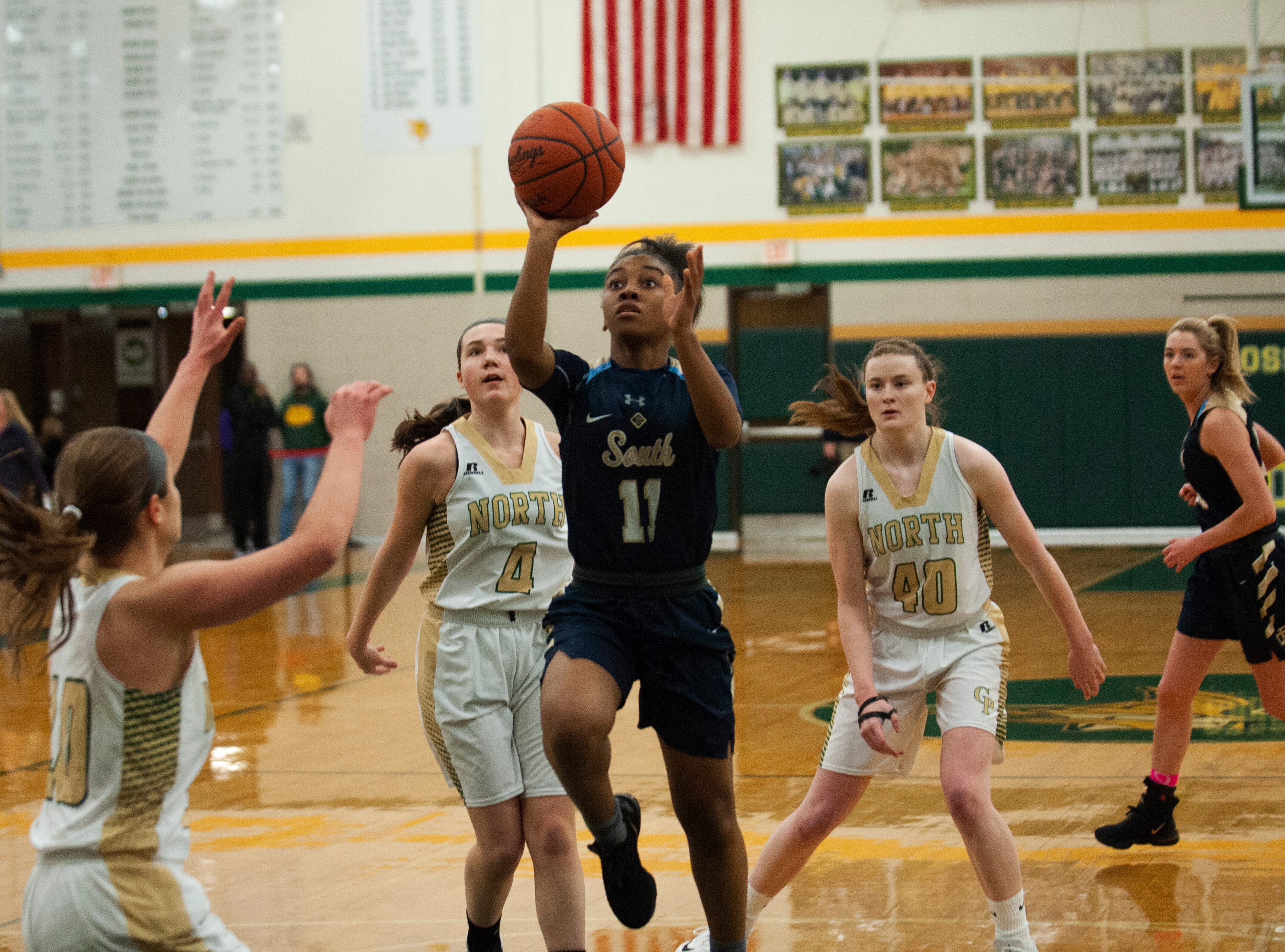 Grosse Pointe South's Sydni Hall goes up for a shot in the paint against Grosse Pointe North defenders during the first half at Grosse Pointe North High School  on Friday, March 8, 2019.
