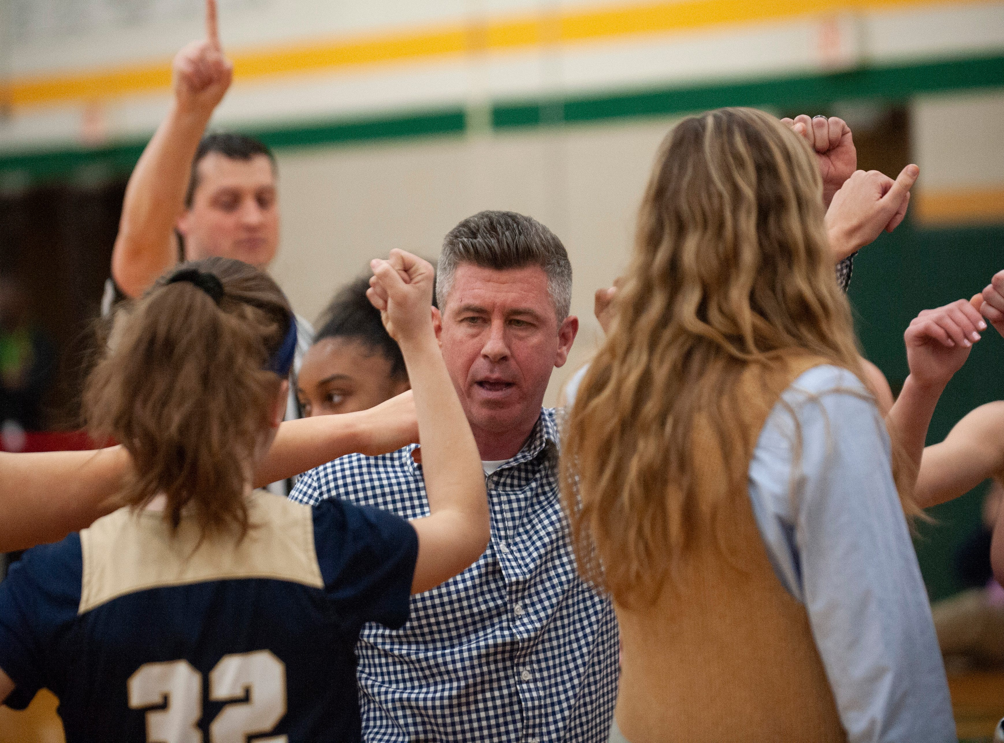 Grosse Pointe South head coach Kevin Richards gathers his Blue Devils together during a timeout in the first half.