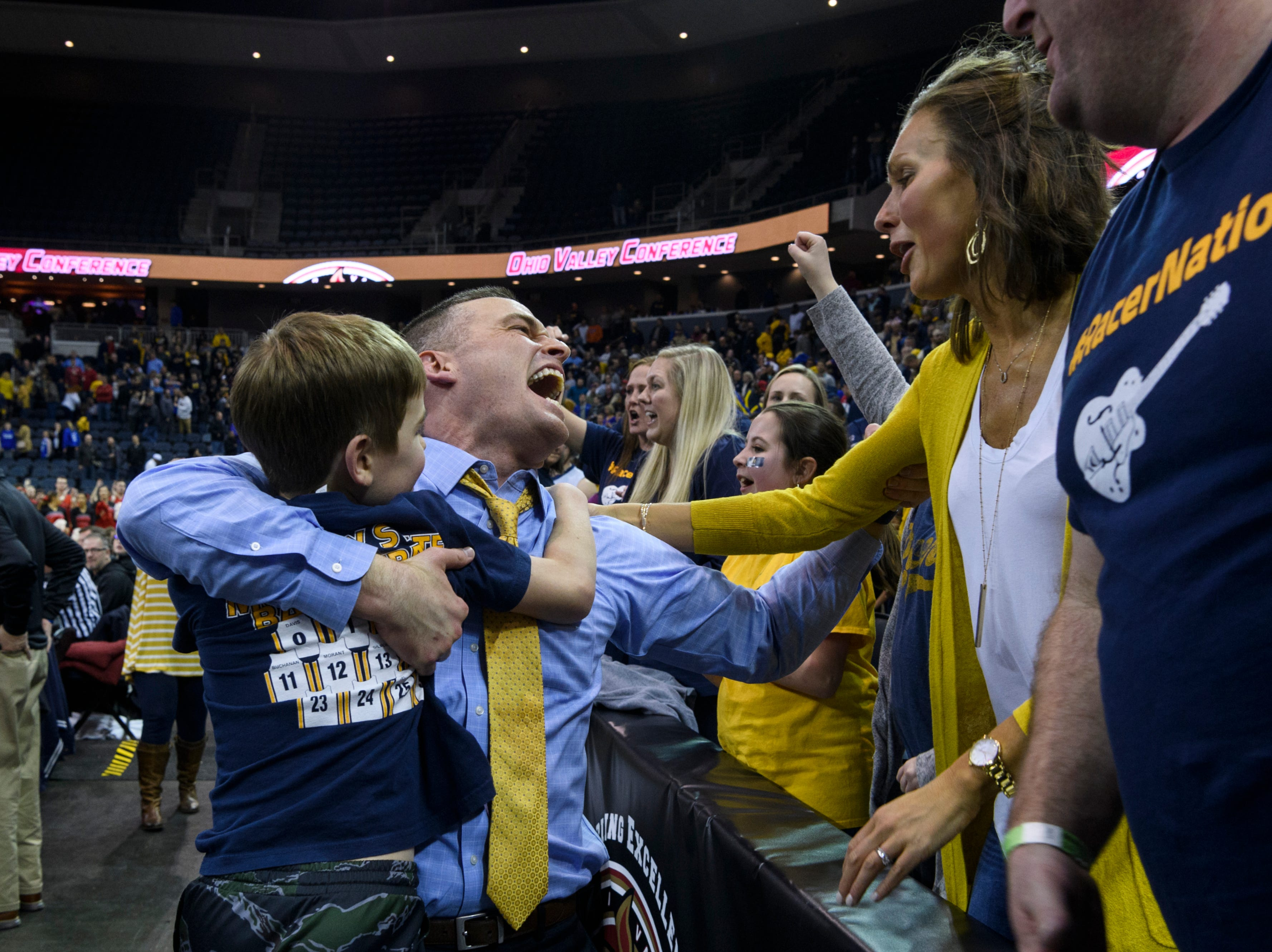 Matt McMahon, center, Murray State Racers Head Coach, celebrates the team's 76-74 win with his son Mason, 7, and wife Mary McMahon during the Ohio Valley Conference tournament semifinals against the Jacksonville State University Gamecocks at Ford Center in Evansville, Ind., Friday, March 8, 2019. The Racers will advance to Saturday's OVC Championship against the Belmont Bruins.