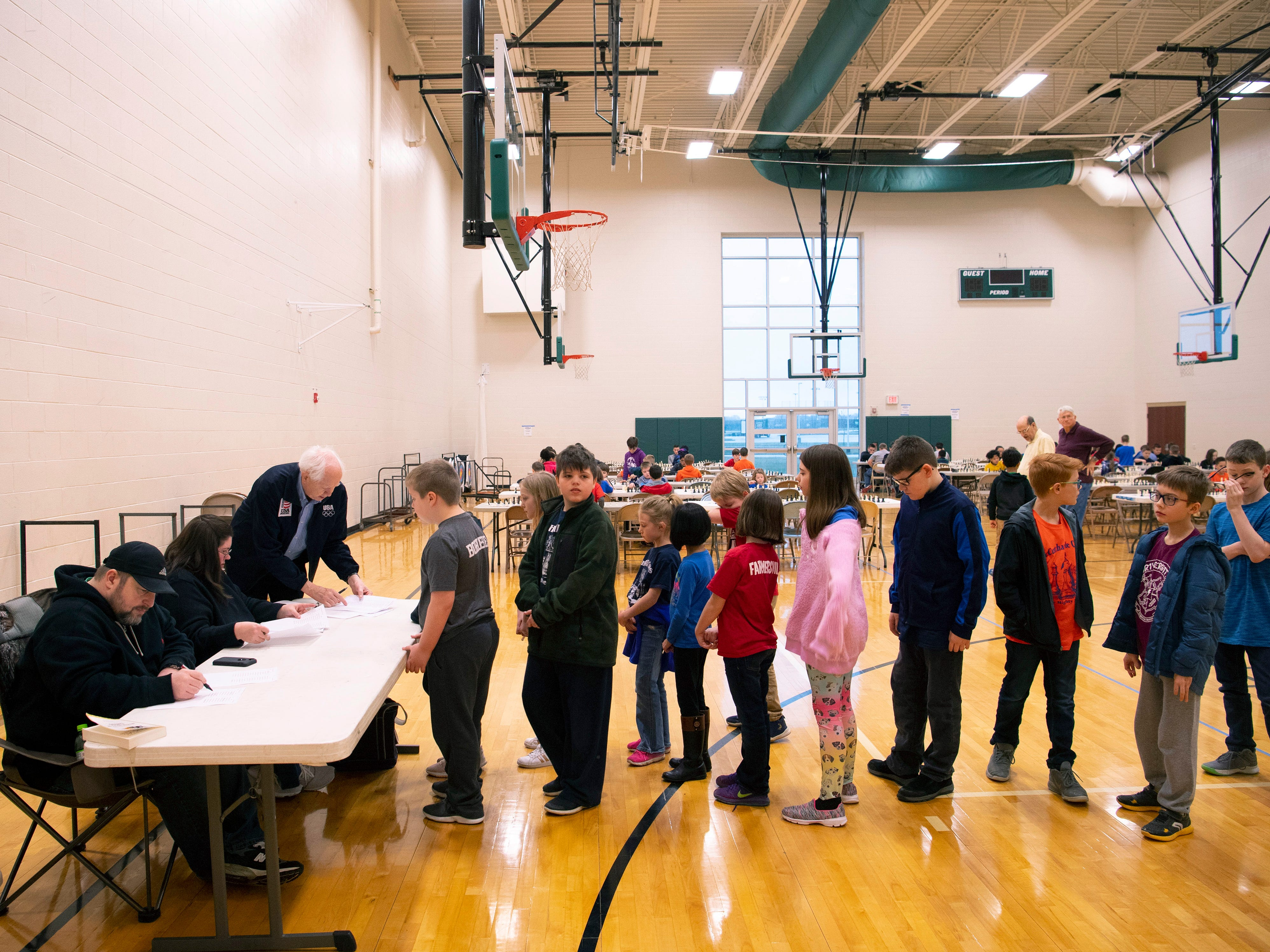 Participants wait their turns to record their match results at the K-12 Spring Scholastic Chess Tournament at North Junior High School Saturday.