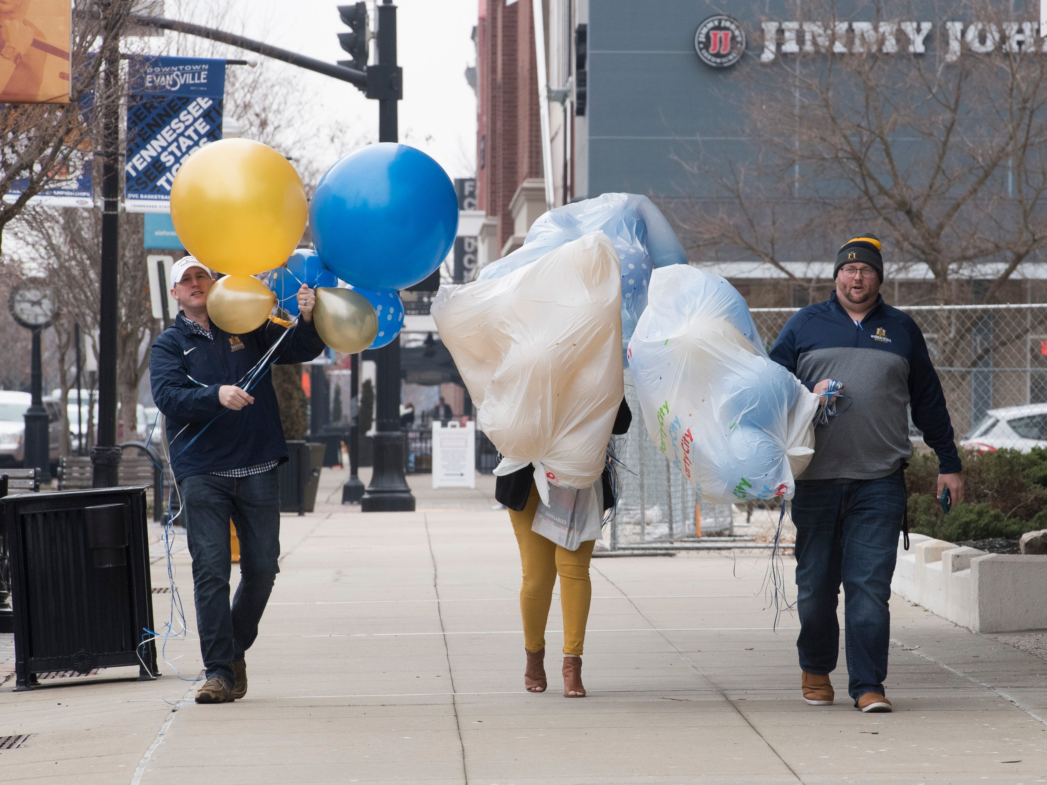 Austin Wyatt, left, Amy Wyatt, middle, and Brock Rydecki, right, carry balloons down Main Street in Downtown Evansville to decorate Kevin's Backstage Bar and Grill for the Murray State pregame party before the Racers take on the Jacksonville Gamecocks in the Ohio Valley Conference Tournament at the Ford Center in Evansville, Ind., Friday, March 8, 2019.