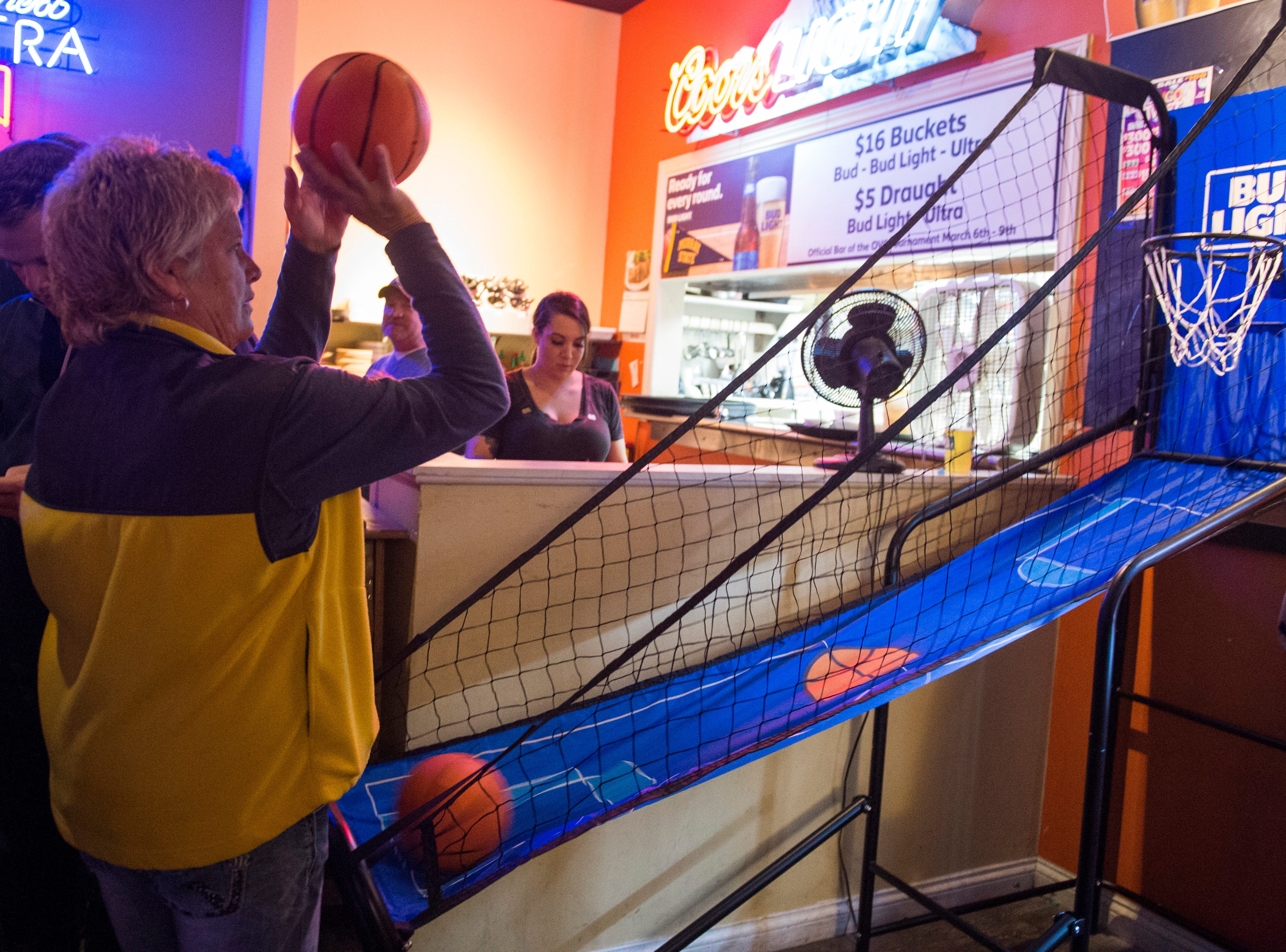 Murray State fan Cana Sheridan takes time to practice her shot at Kevin's Backstage Bar and Grill before heading to the game Friday, March 8,  2019.