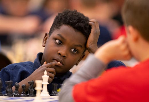 D'ahjea Fetrell, 8, The Joshua Academy, and Alex Cameron, 8, Cynthia Heights Elementary School, compete in the K-12 Spring Scholastic Chess Tournament at North Junior High School Saturday.