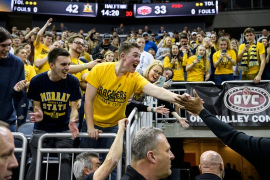 Tate Burris, center, reacts to receiving a high-five from