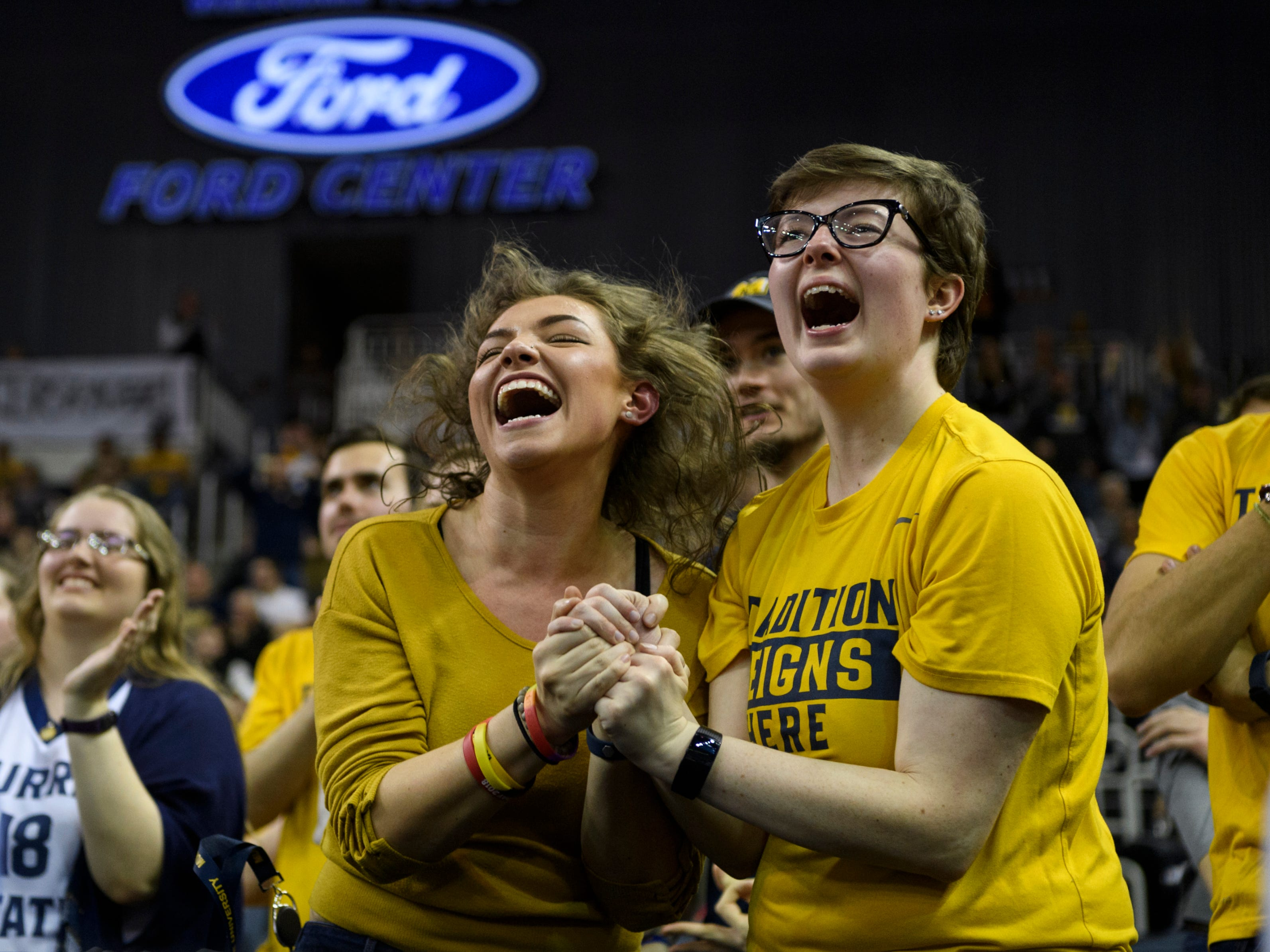 Student fans Kelsay Goldsberry and Amber Miller cheer for the Murray State University Racers during the Ohio Valley Conference tournament semifinal match up against the Jacksonville State University Gamecocks at Ford Center in Evansville, Ind., Friday, March 8, 2019.