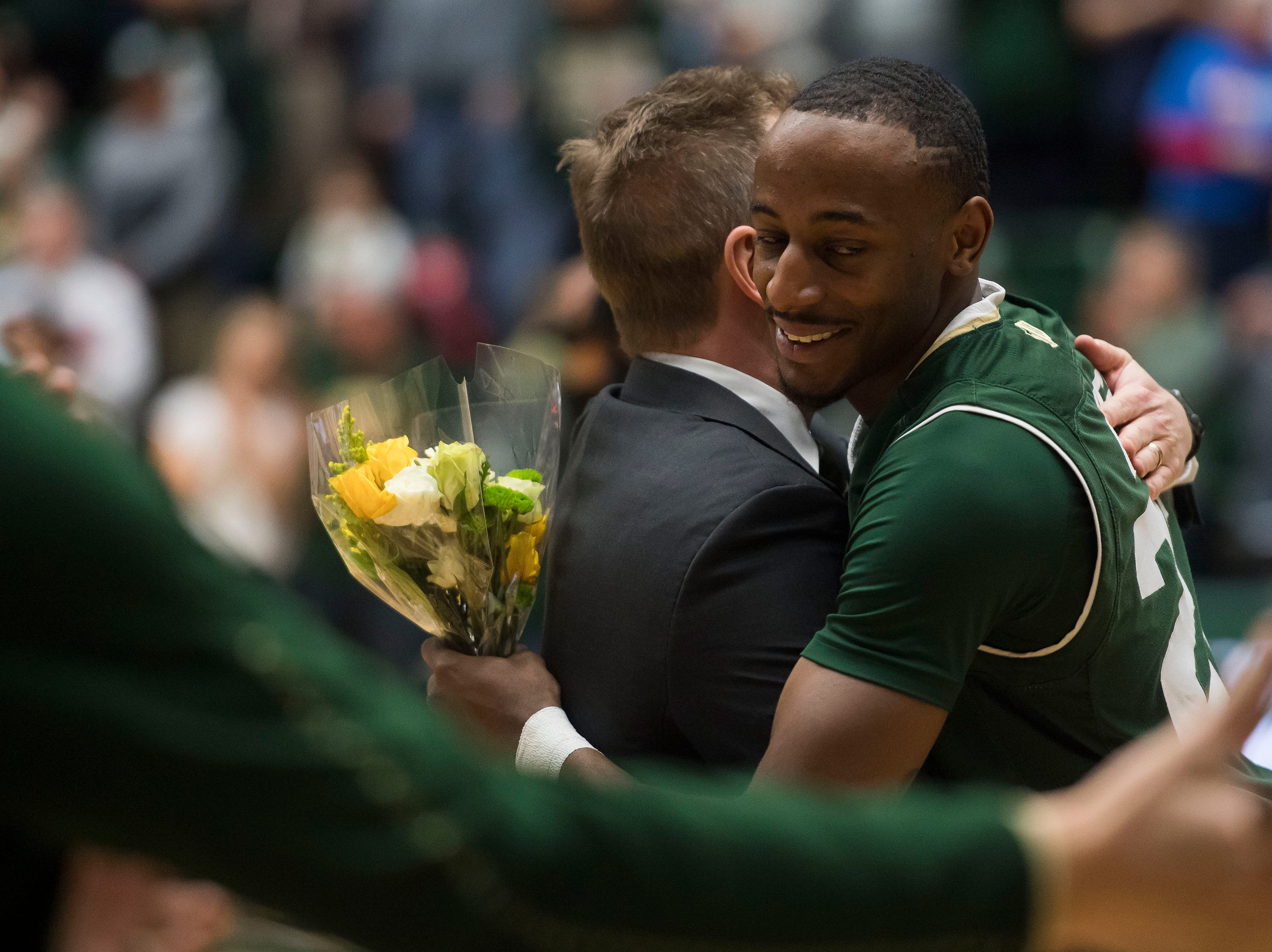 Colorado State University senior guar J.D. Paige hugs head coach Niko Medved while being honored before a game against University of Nevada, Las Vegas on Saturday, March 9, 2019, at Moby Arena in Fort Collins, Colo.