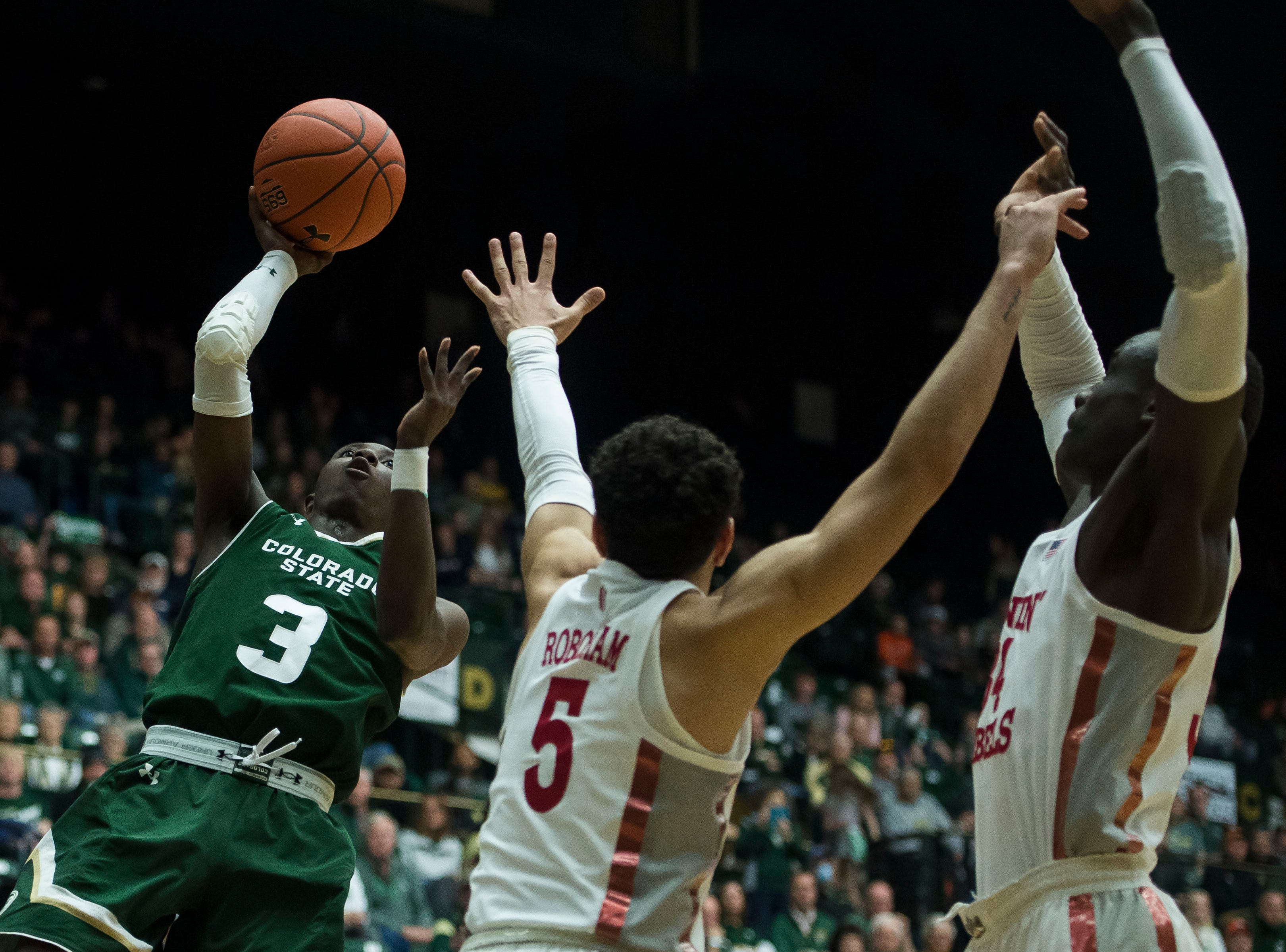 Colorado State University freshman guard Kendle Moore (3) puts a shot up over University of Nevada Las Vegas senior guard Noah Robotham (5) on Saturday, March 9, 2019, at Moby Arena in Fort Collins, Colo.