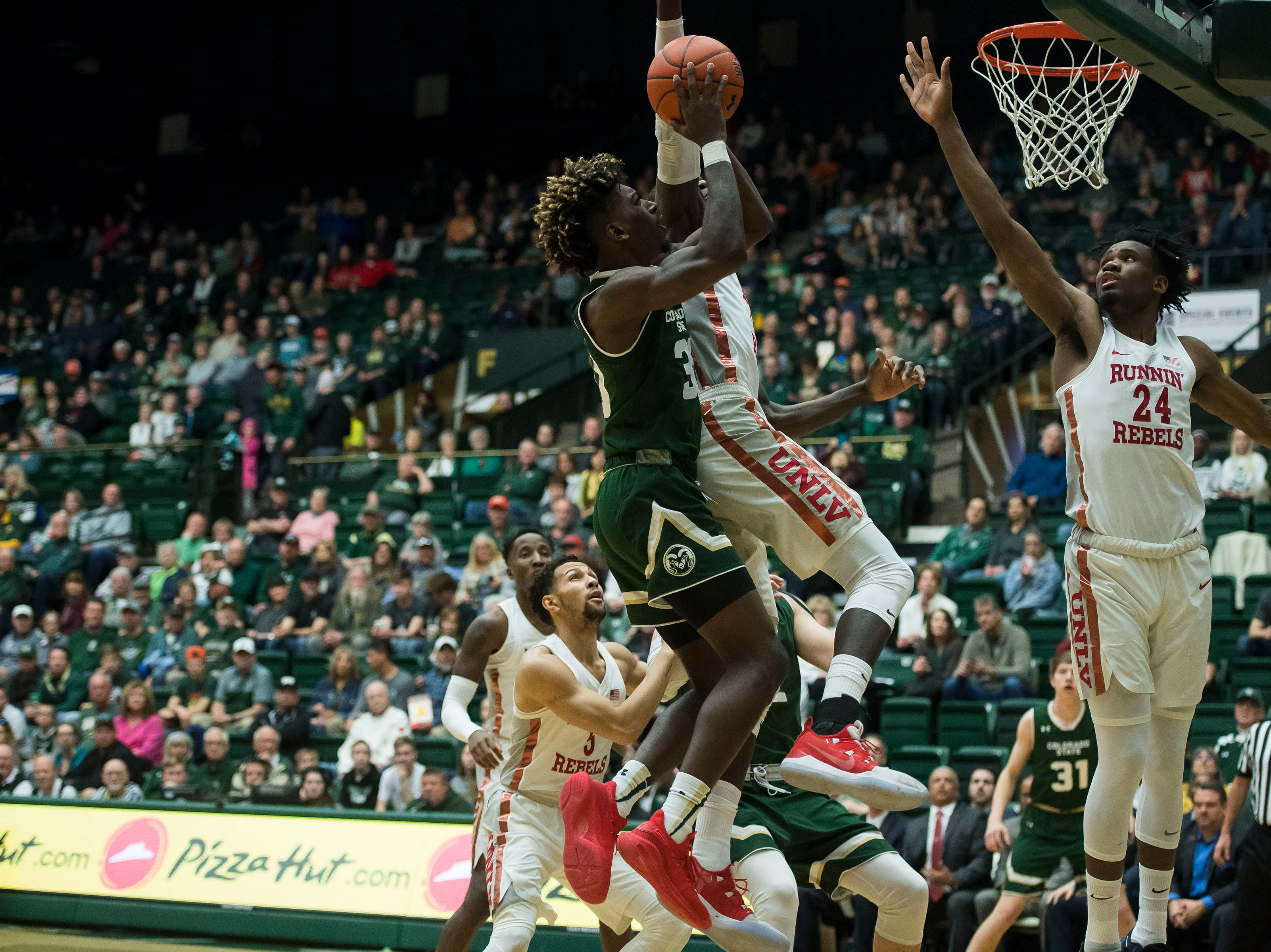 Colorado State University junior guard Kris Martin (30) attempts a shot against University of Nevada Las Vegas freshman forward Joel Ntambwe (24) on Saturday, March 9, 2019, at Moby Arena in Fort Collins, Colo.