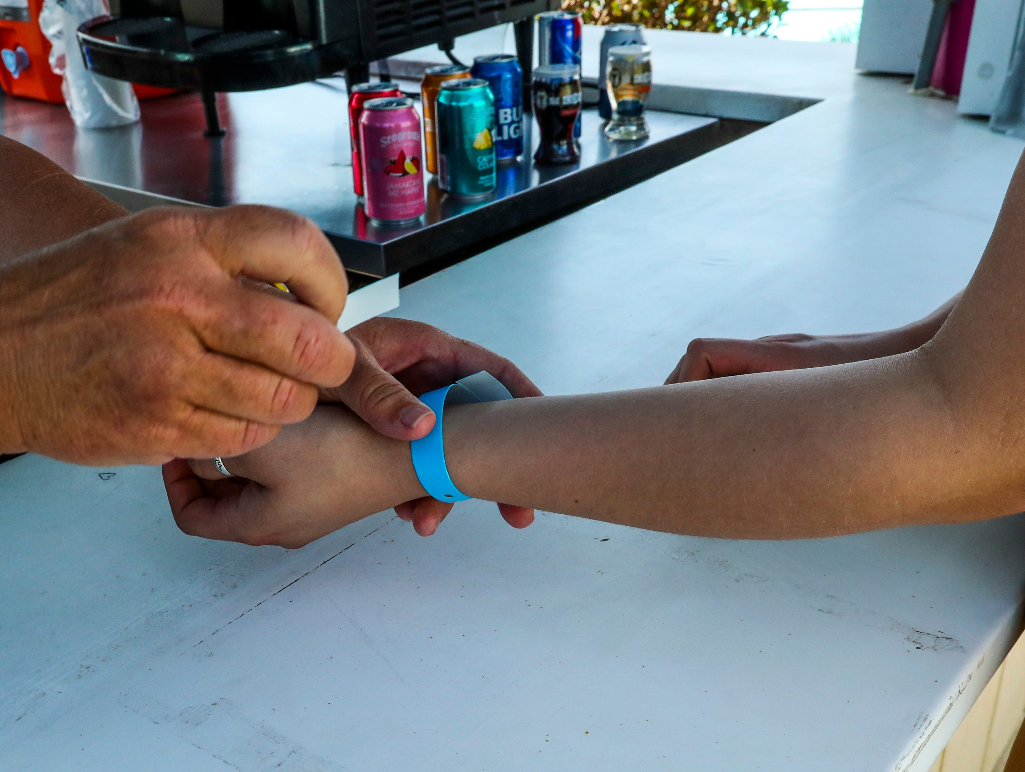 Kate Gehin pulls a ticket off the wristband of Madison Flood, 21, visiting from Michigan. Alcohol sales have been steady on the opening day. Sun Splash is opening for it's 2019 season - the first season that will include sales of beer, wine and wine smoothies. Blue wrist bands are handed out after showing your license. The wrist band has two tickets on it. Each person is allowed two drinks. The wine slushes were are popular item to drink.