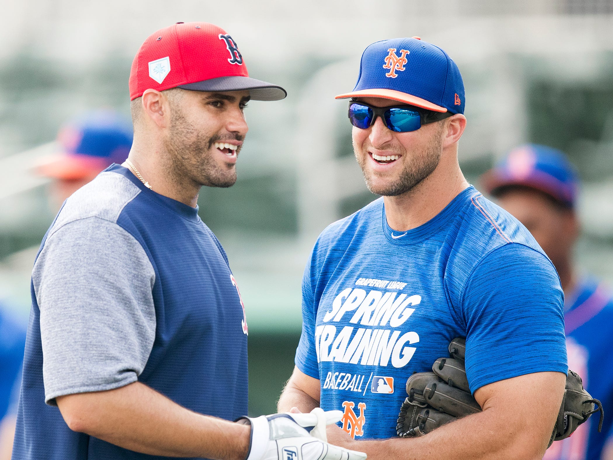 Boston Red Sox J.D. Martinez, left, and New York Mets' Tim Tebow relax before their spring training game on Saturday at JetBlue Park in Fort Myers.