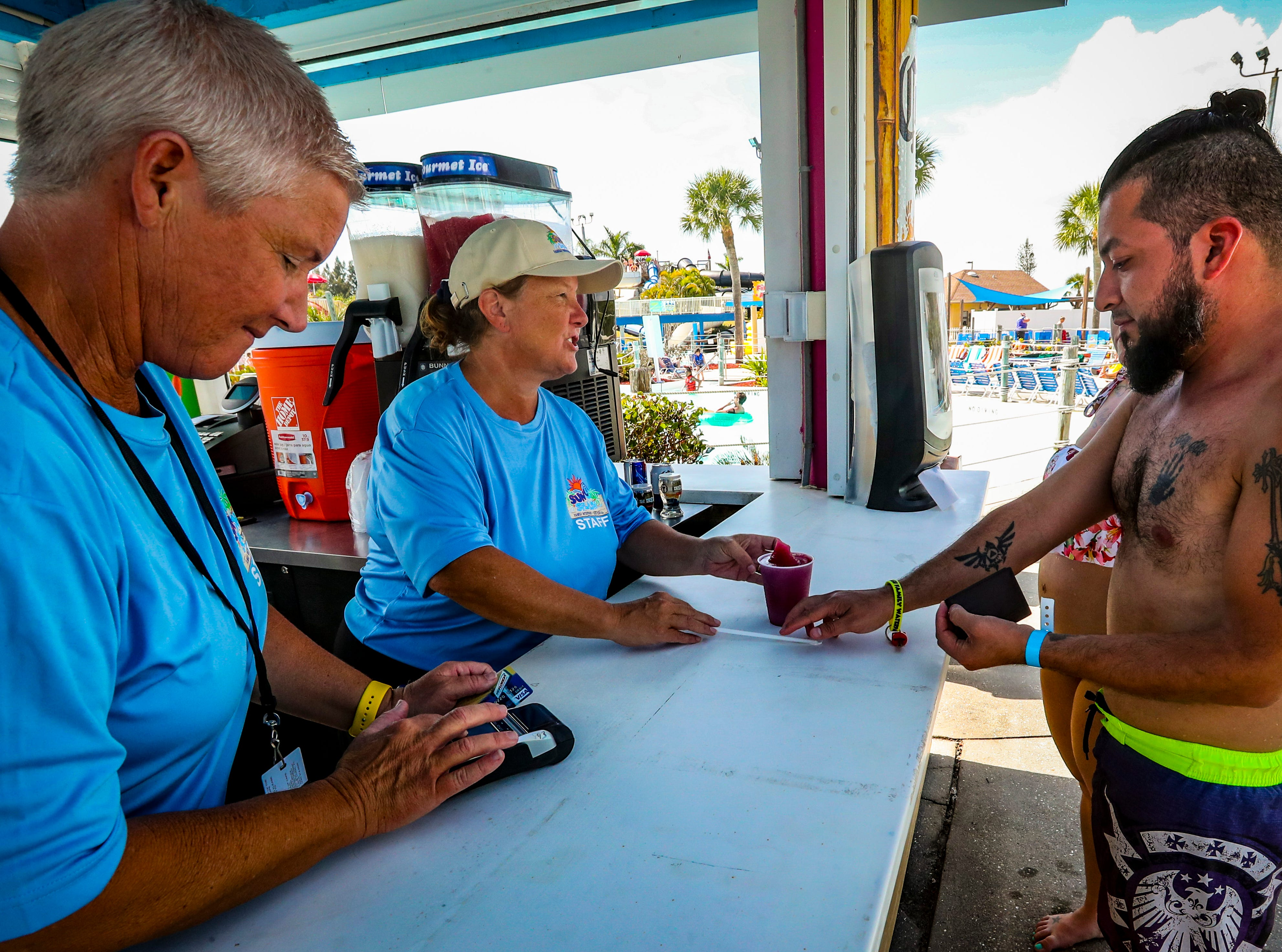 Jonathan Flores, 32, of Arcadia, reaches for his drink. He was in favor of alcohol being served at the water park and bought a wine slush. (left) Kate Gehin and Letty Garcia serve him. Sun Splash is opening for it's 2019 season - the first season that will include sales of beer, wine and wine smoothies. Blue wrist bands are handed out after showing your license. The wrist band has two tickets on it. Each person is allowed two drinks. The wine slushes were are popular item to drink.