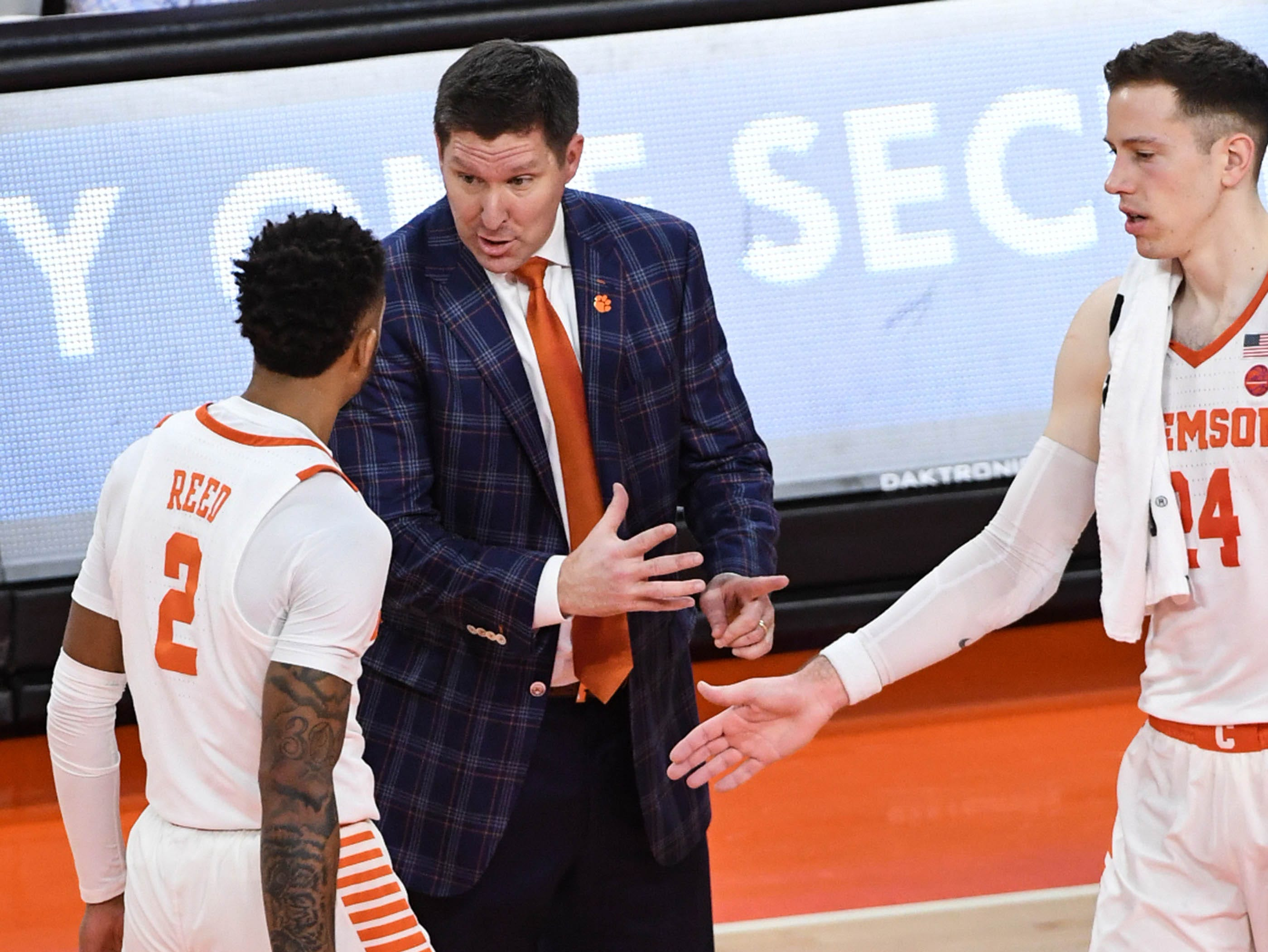 Clemson head coach Brad Brownell  talks with Clemson guard Marcquise Reed (2) near forward David Skara (24), right,during the first half in Littlejohn Coliseum in Clemson Saturday, March 9, 2019.