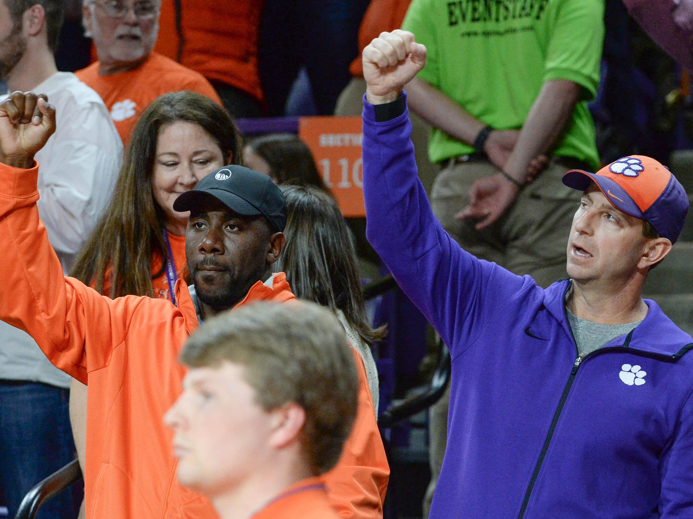 Former Clemson football player C.J. Spilller, left, and Clemson football coach Dabo Swinney cheer during the second half in Littlejohn Coliseum in Clemson Saturday, March 9, 2019.