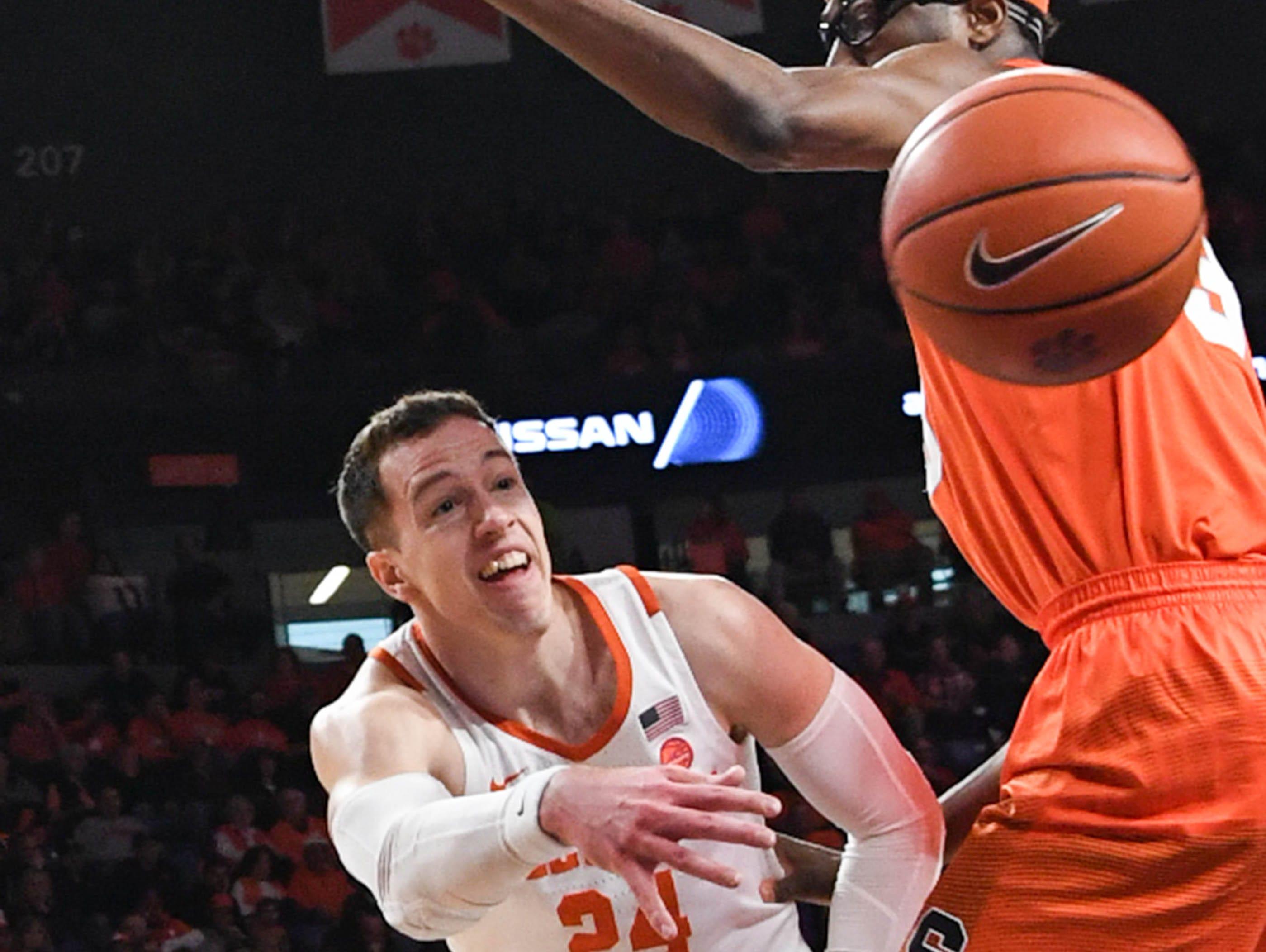 Clemson forward David Skara (24) passes around Syracuse forward Elijah Hughes(33) during the first half in Littlejohn Coliseum in Clemson Saturday, March 9, 2019.