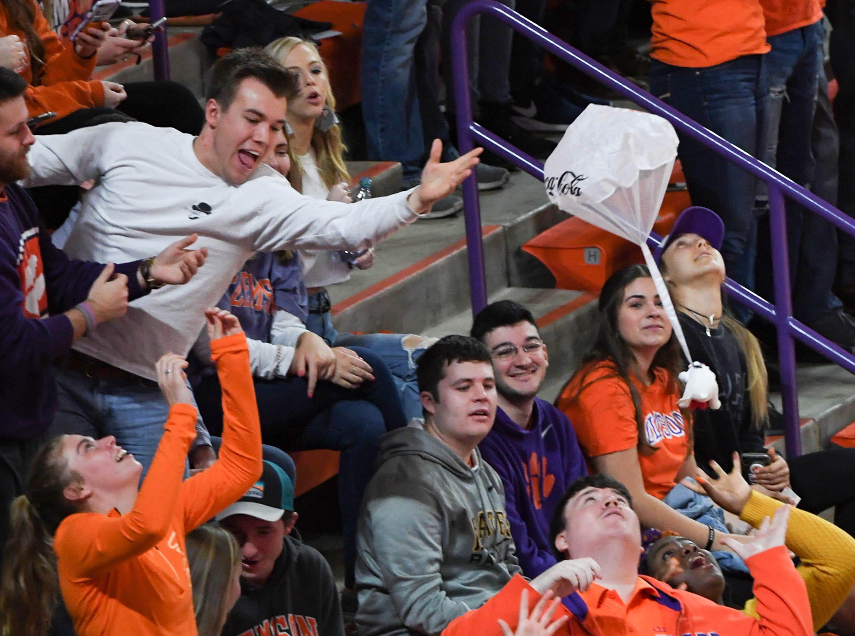 Clemson fans reach for toys with parachutes dropping from the catwalk in a break at the Syracuse game, during the first half in Littlejohn Coliseum in Clemson Saturday, March 9, 2019.