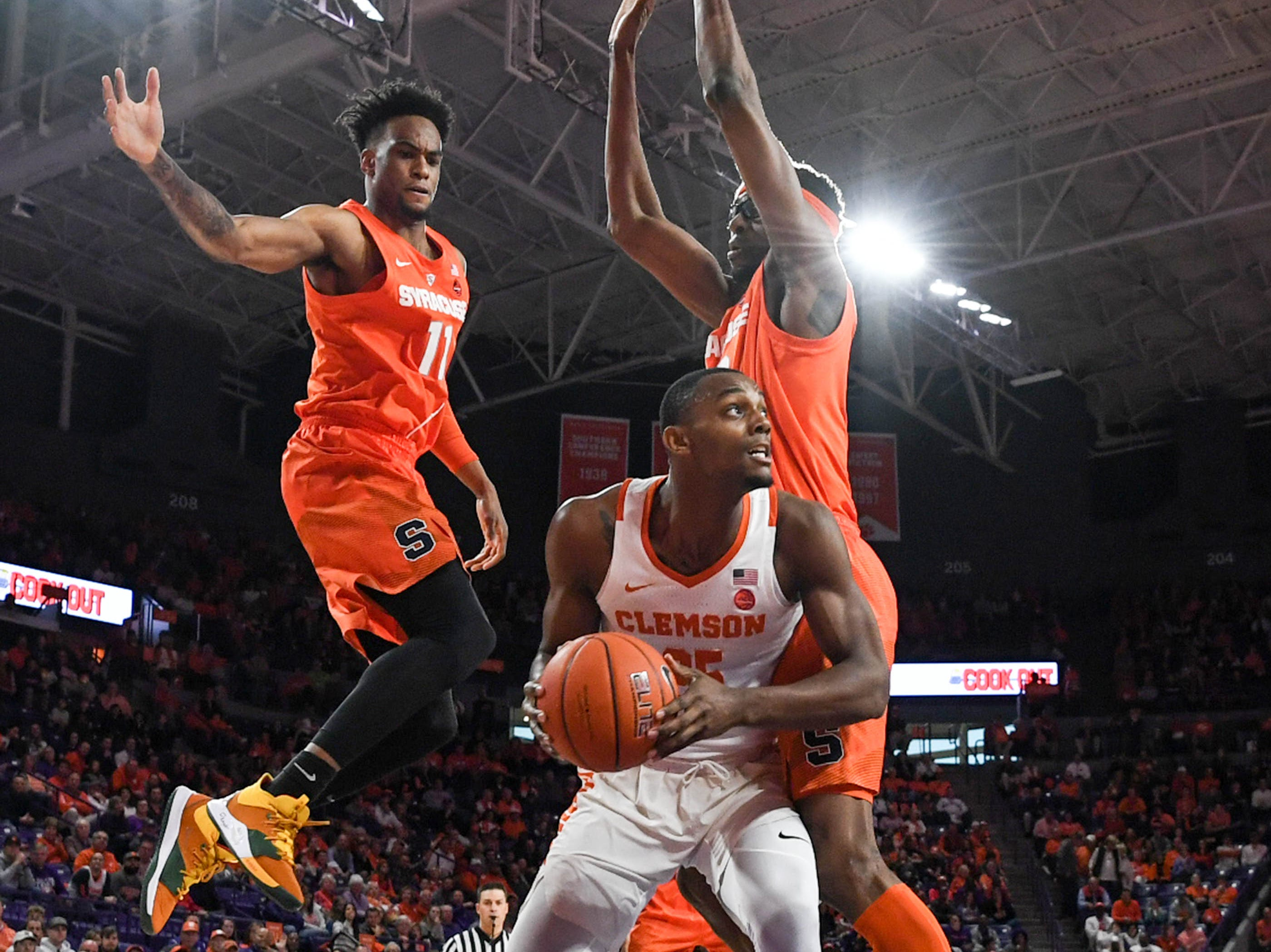 Clemson forward Aamir Simms (25) looks for an opportunity to shoot near Syracuse forward Oshae Brissett(11), left, and Syracuse center Paschal Chukwu(13) during the first half in Littlejohn Coliseum in Clemson Saturday, March 9, 2019.