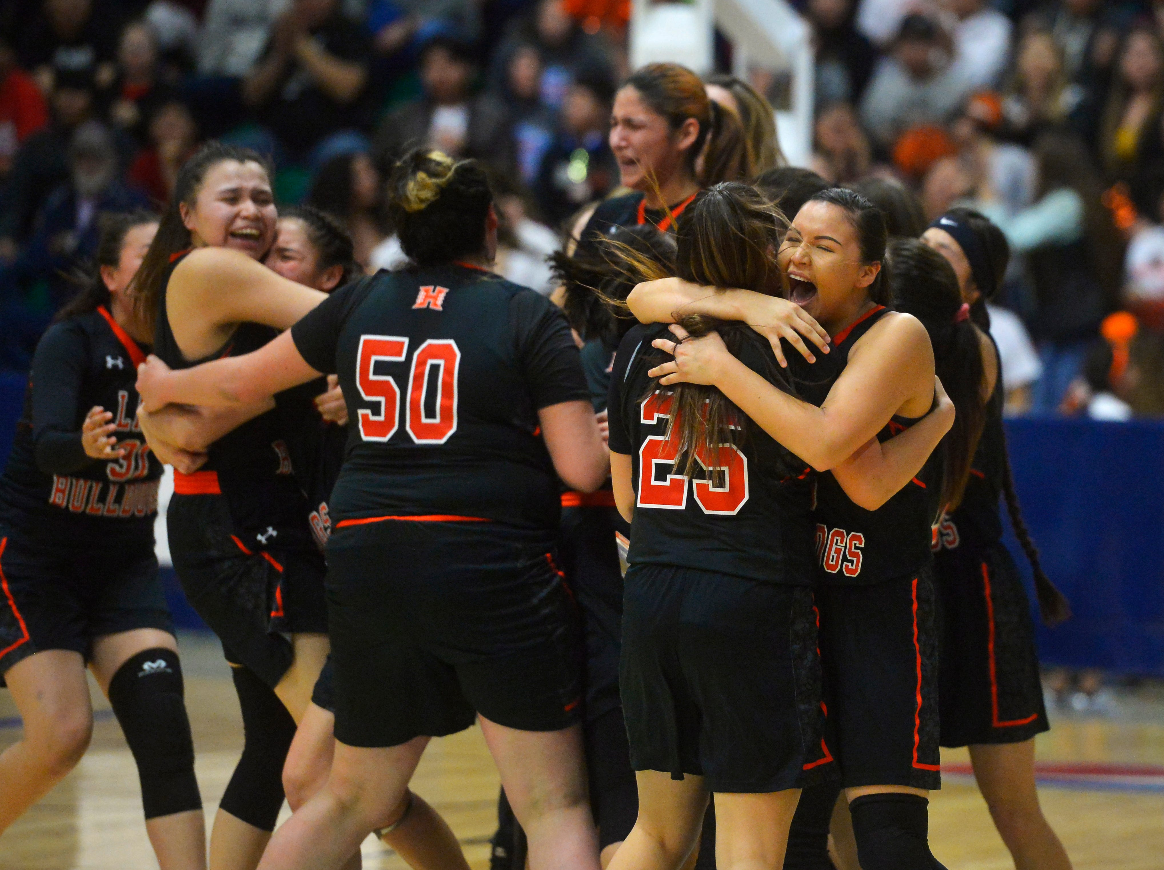 The Hardin girls celebrate their semifinal victory over Billings Central in the semifinal game of the State Class A Basketball Tournament in the Four Seasons Arena, Friday.