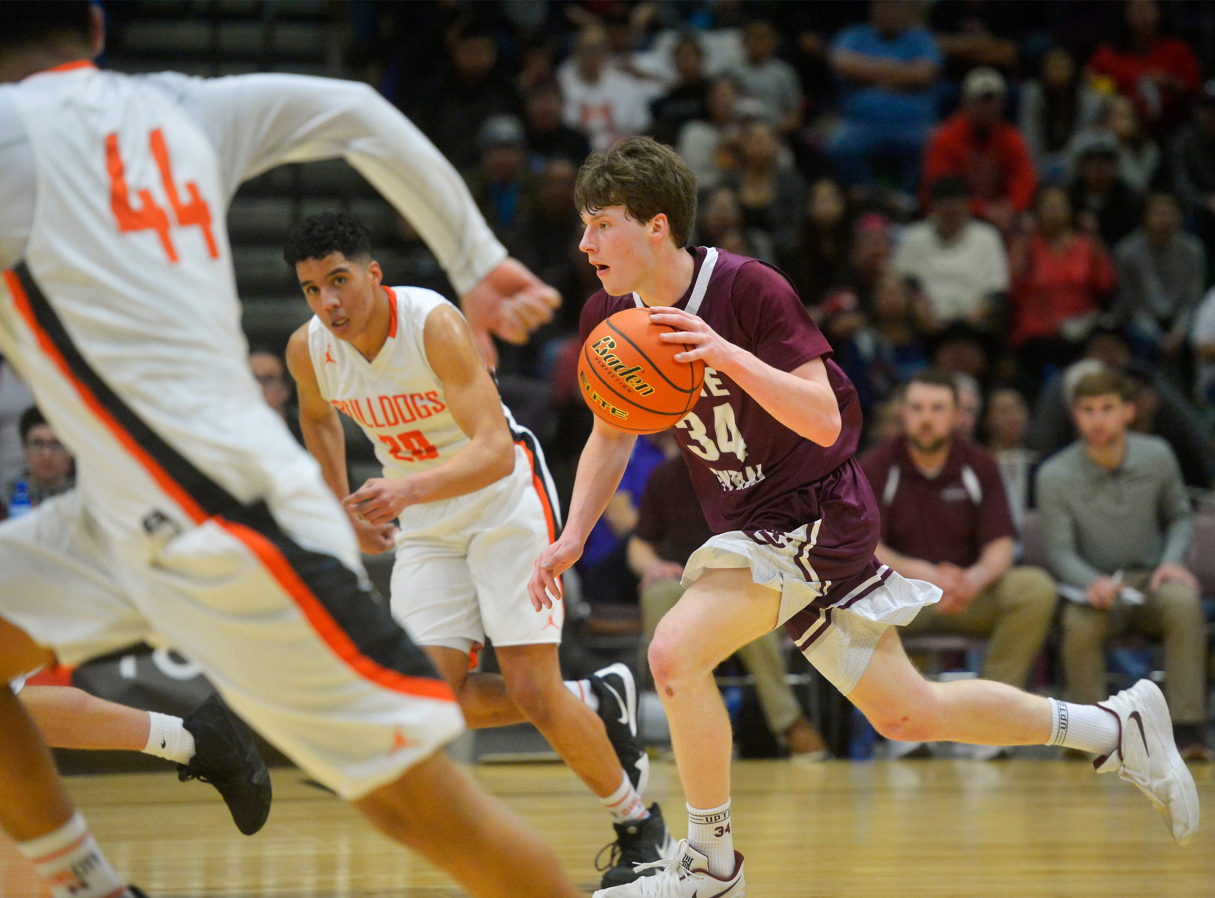 Butte Central's Cade Holter pushes the ball up the floor during the semifinal game against Hardin at the State Class A Basketball Tournament in the Four Seasons Arena, Friday.