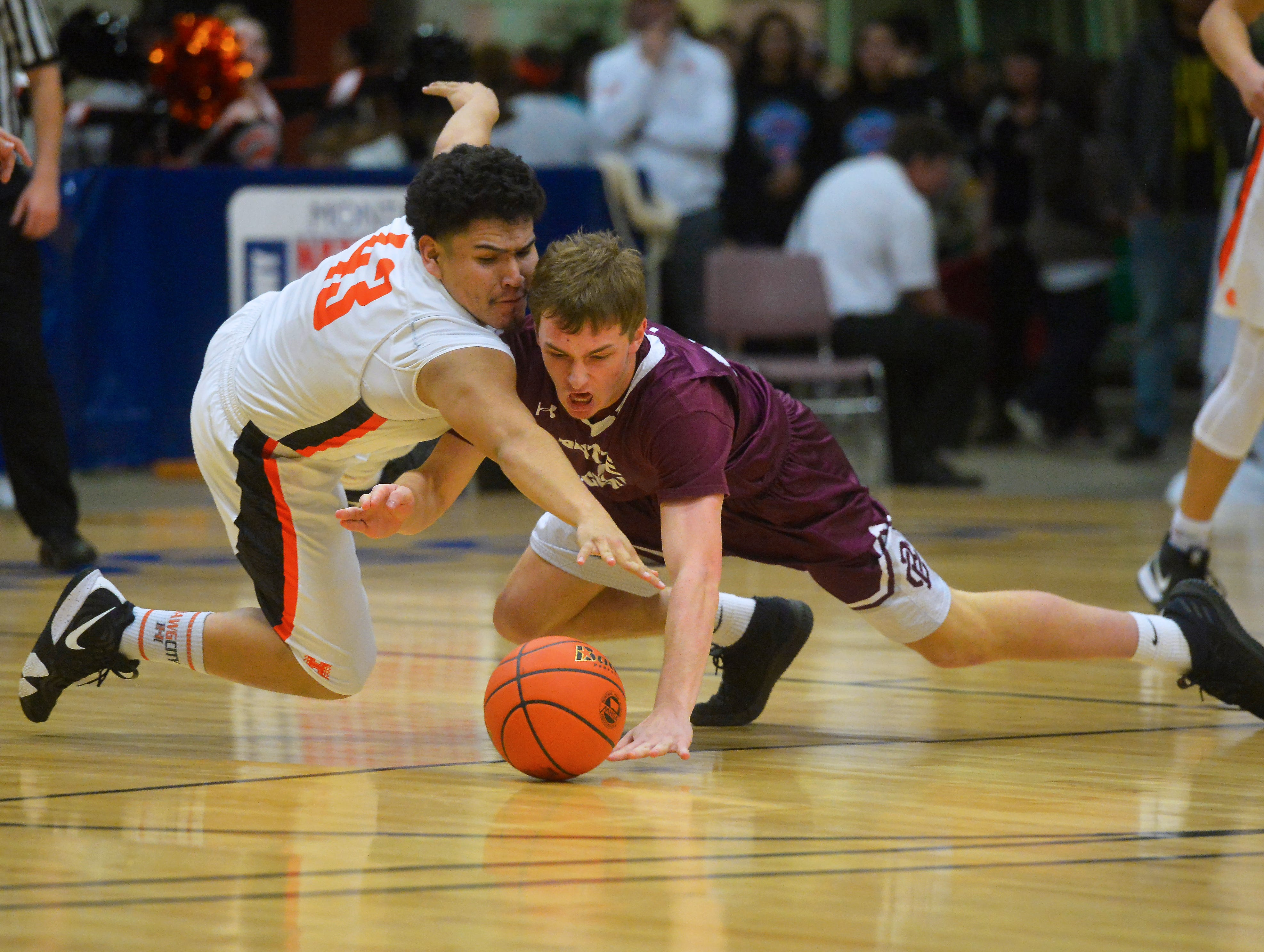 Hardin's Andrew House and Butte Central's Matt Simkins dive for a loose ball during the semifinal game of the State Class A Basketball Tournament in the Four Seasons Arena, Friday.