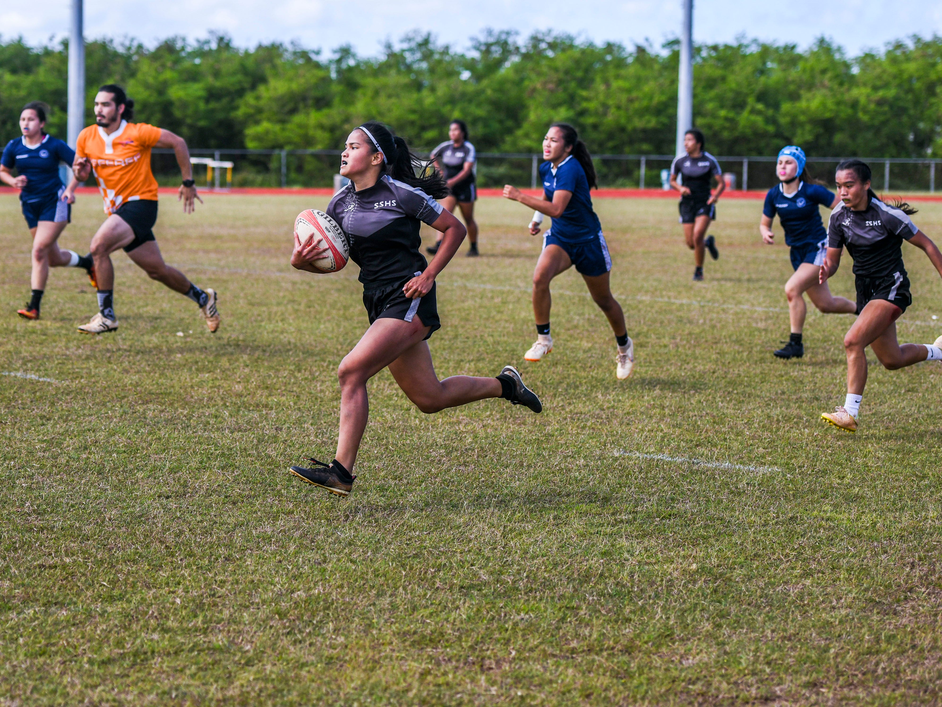 The Simon Sanchez High School Sharks' Angelyn Sobrevilla breaks away on her way to score a try during their Girls Varsity IIAAG/GRFU rugby matchup against the Notre Dame High School Royals on Ramsey Field at the John F. Kennedy High School in Tamuning on Saturday, March 9, 2019. In the end, the Royals defeated the Sharks with a final score of 14-12.