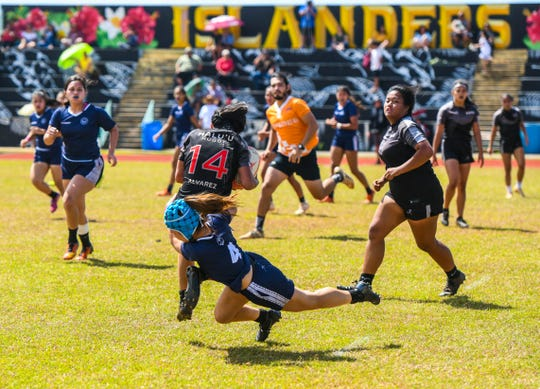 Notre Dame High School Royals' Faith Moylan tackles Simon Sanchez High School Sharks' ball-carrier during an IIAAG/GRFU Girls Varsity Rugby match at Ramsey Field at John F. Kennedy High School in Tamuning in this March 9 file photo.