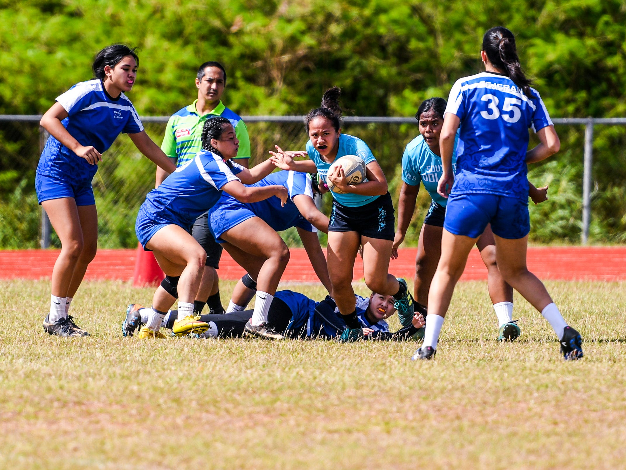 The Academy of Our Lady Guam Cougars competes against the Southern High School Dolphins during their Girls Varsity IIAAG/GRFU rugby matchup on Ramsey Field at the John F. Kennedy High School in Tamuning on Saturday, March 9, 2019. In the end, the Dolphins swam away with the victory with a final score of 24-5.