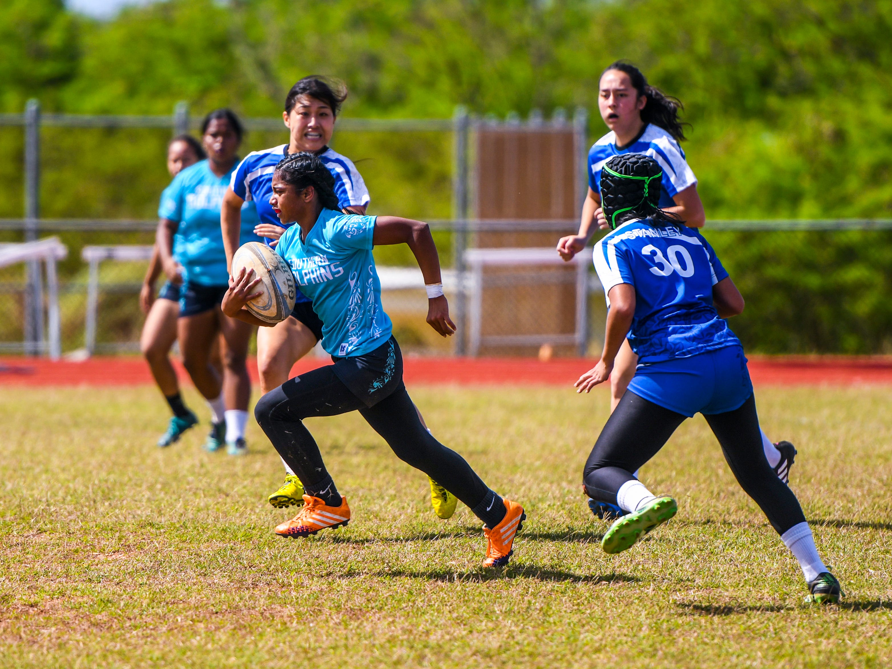 Southern High School Dolphins' Liz Quintanilla bolts down the center to score her second try during a Girls Varsity IIAAG/GRFU rugby matchup with Academy of Our Lady Guam Cougars on Ramsey Field at the John F. Kennedy High School in Tamuning on Saturday, March 9, 2019. In the end, the Dolphins swam away with the victory with a final score of 24-5.