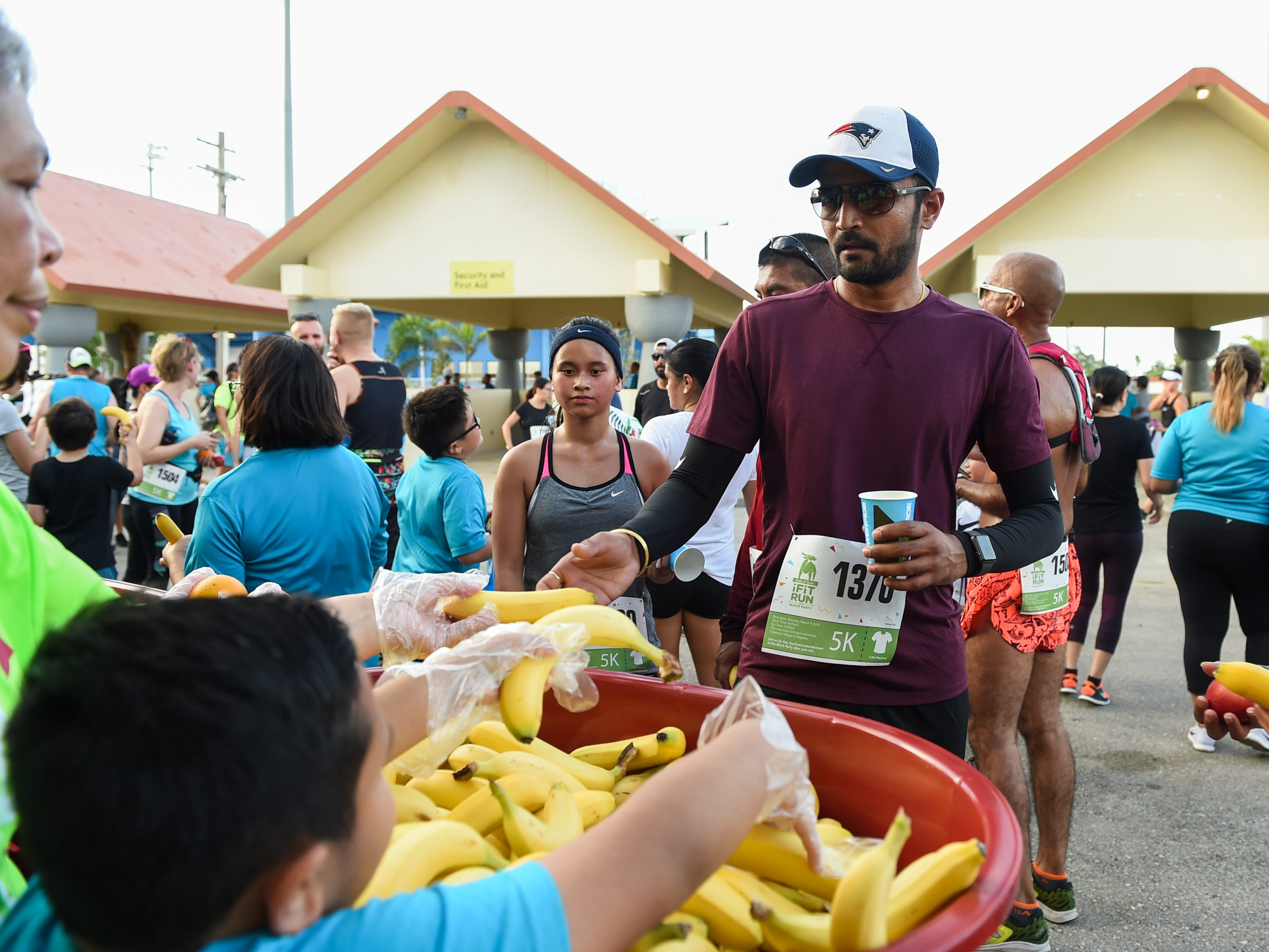Race participants receive free fruits during the Bank of Guam Ifit Run and Block Party at at Chamorro Village in Hagåtña, March 9, 2019.
