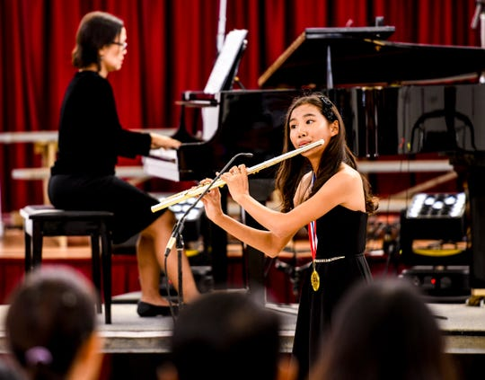 Kayley Kang of St. John's School performs on her flute during the Tumon Bay Music Festival Encore Finale Concert and Award Ceremony at the center court of Micronesia Mall in this March 9, 2019, file photo.