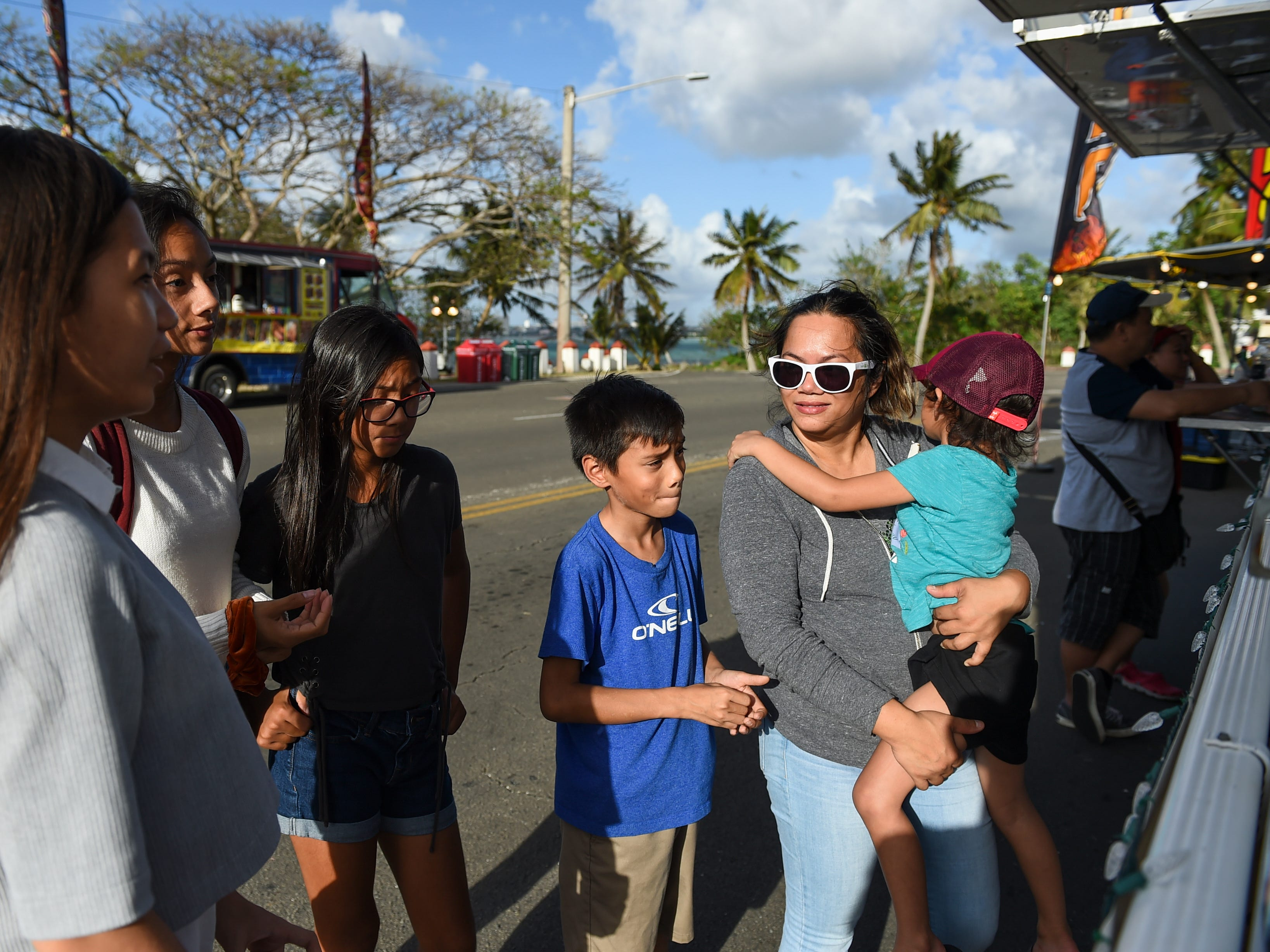 A family places an order at a food truck during the Bank of Guam Ifit Run and Block Party at Chamorro Village in Hagåtña, March 9, 2019.
