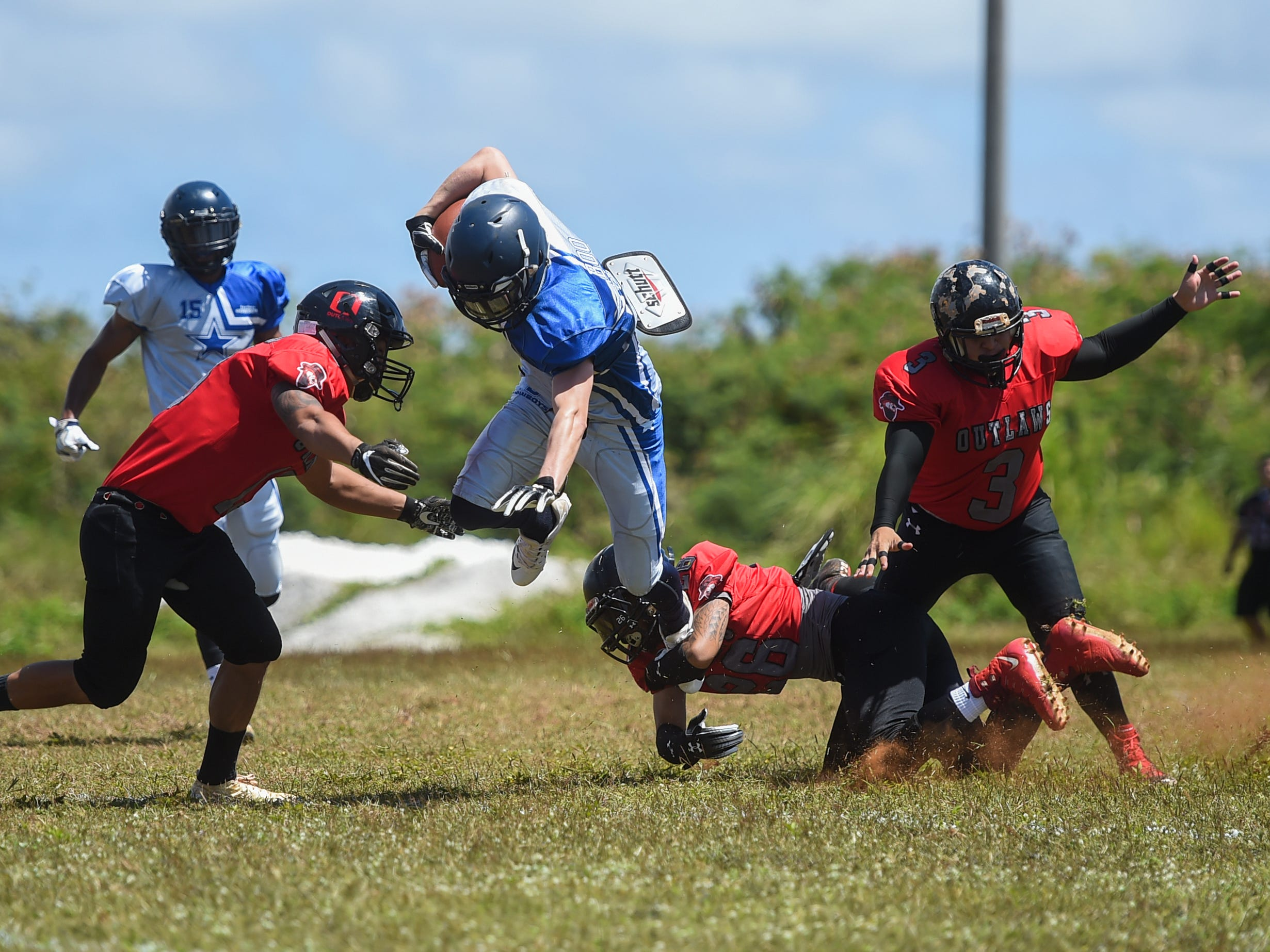 """Southern Cowboys player Chance """"Boo"""" Benefield attempts to elude a tackle by an Outlaws player during a Budweiser Guahan Varsity Football League game at Eagles Field in Mangilao, March 9, 2019."""