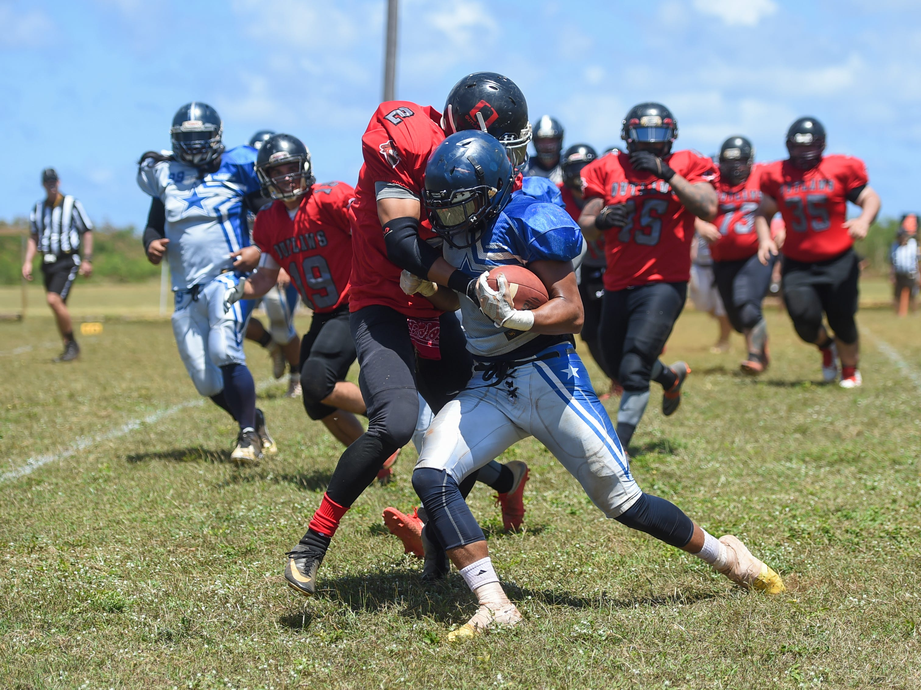 Outlaws player Joel Limtiaco (2) attempts to bring down the Southern Cowboys' Connie Toney during a Budweiser Guahan Varsity Football League game at Eagles Field in Mangilao, March 9, 2019.