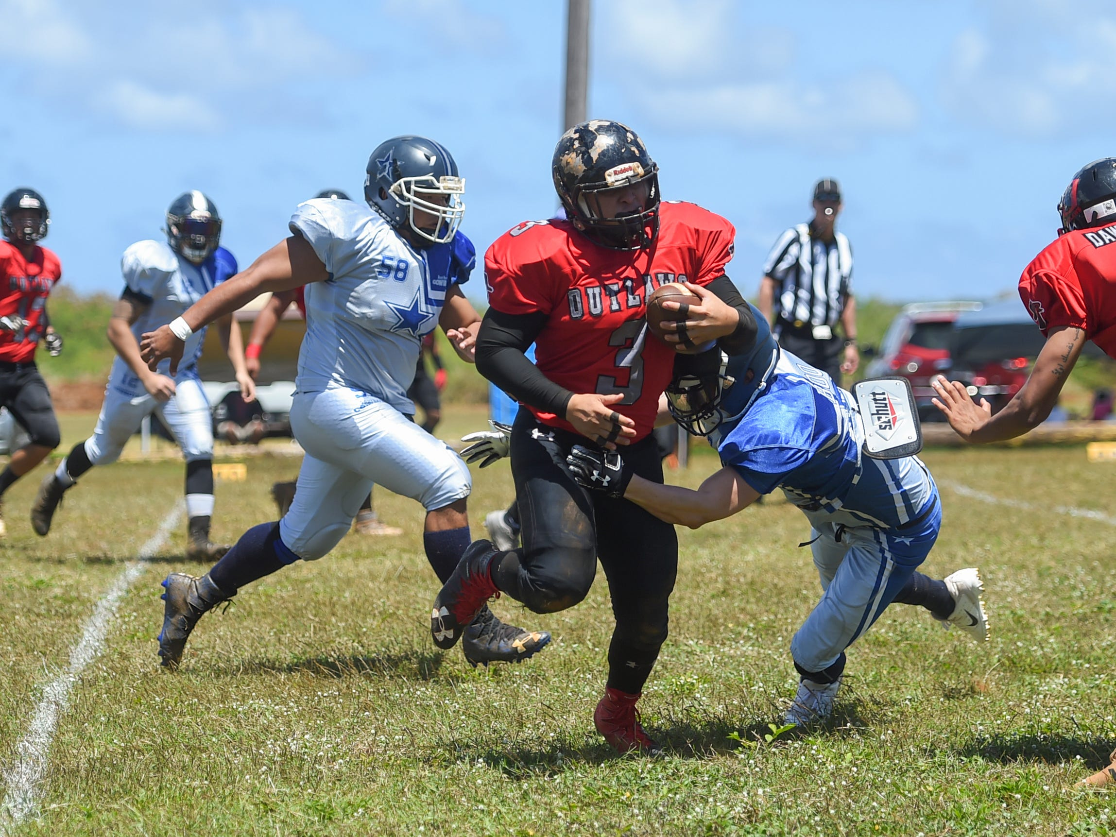 Outlaws player Frankie Fernandez (3) runs the ball against the Southern Cowboys during a Budweiser Guahan Varsity Football League game at Eagles Field in Mangilao, March 9, 2019.