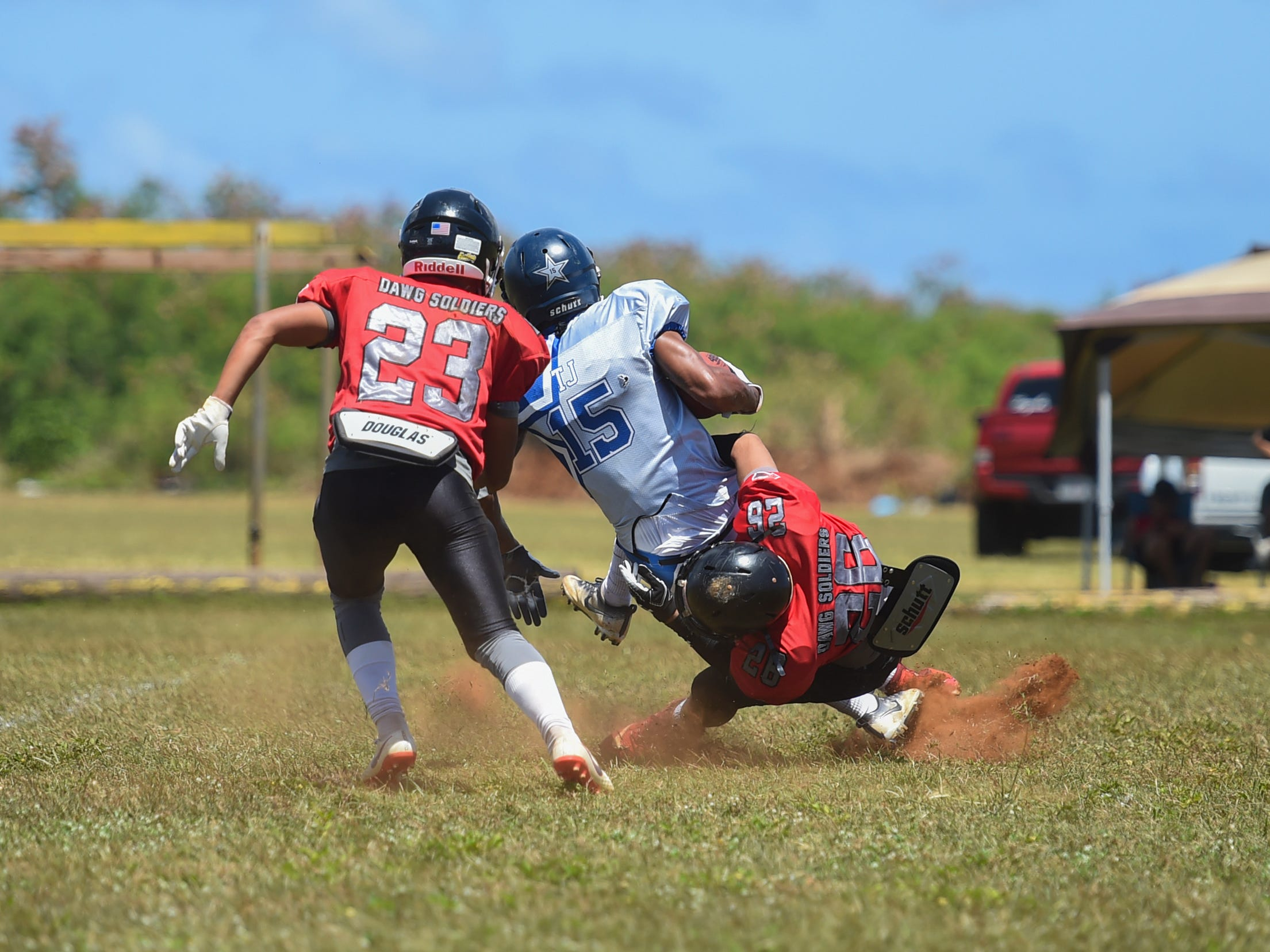 The Outlaws' Lance Borja (26) tackles a Southern Cowboys player during a Budweiser Guahan Varsity Football League game at Eagles Field in Mangilao, March 9, 2019.