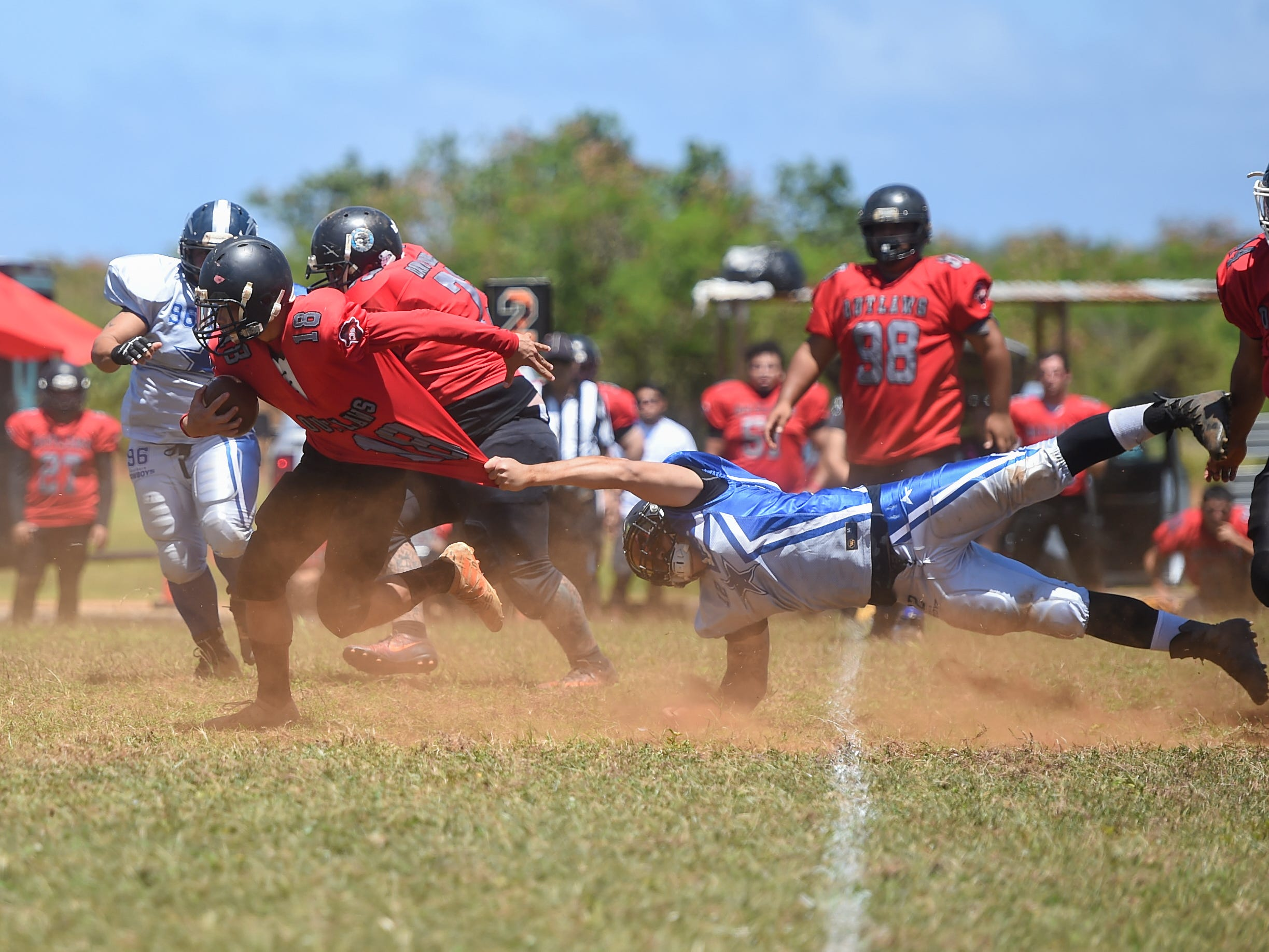 Outlaws player Justin Tanguileg (18) is pursued by Southern Cowboys' Dom Flores (12) during a Budweiser Guahan Varsity Football League game at Eagles Field in Mangilao, March 9, 2019.