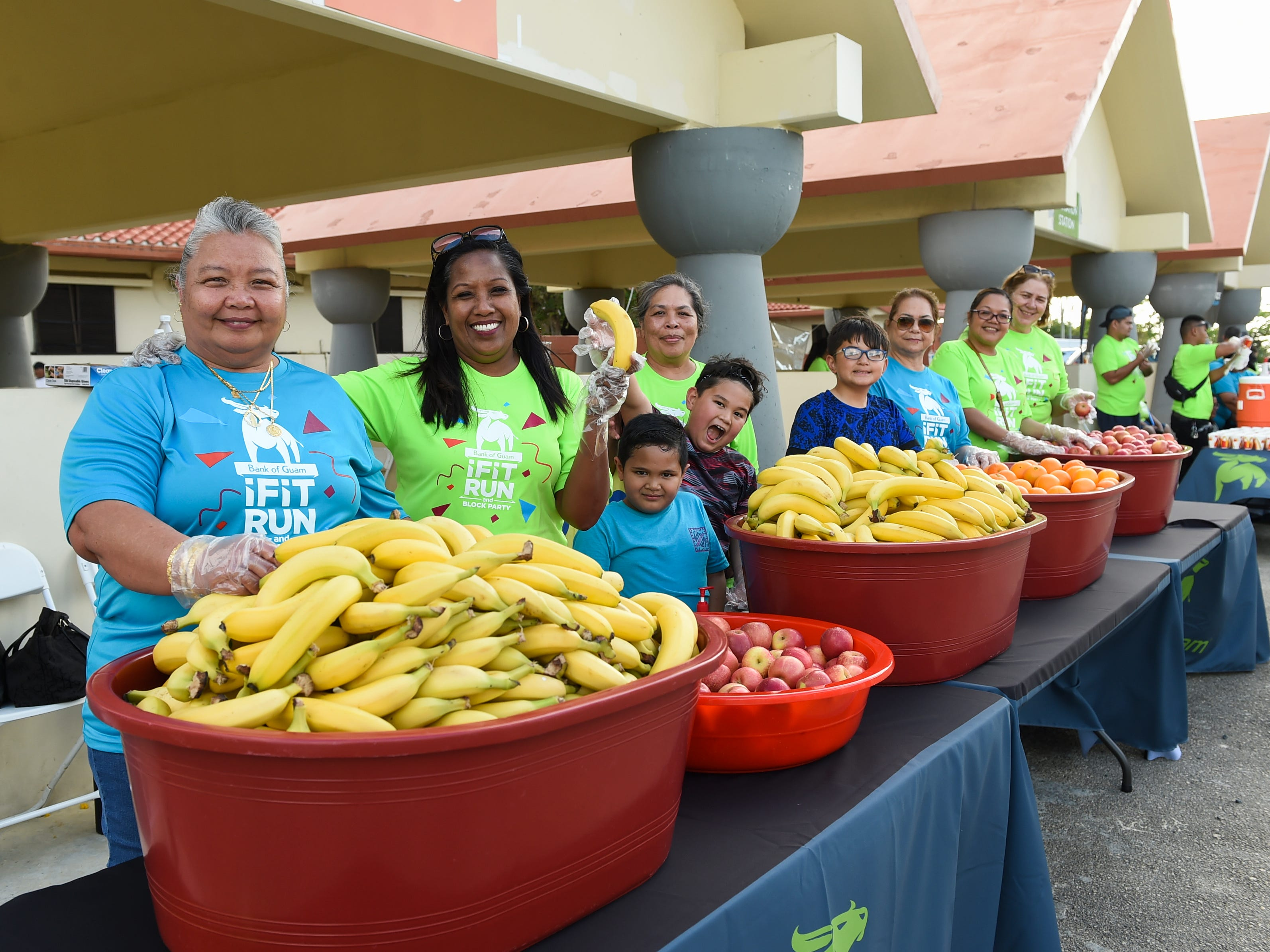 Bank of Guam employees and their family members standby at fruit tables during the Bank of Guam Ifit Run and Block Party at at Chamorro Village in Hagåtña, March 9, 2019.