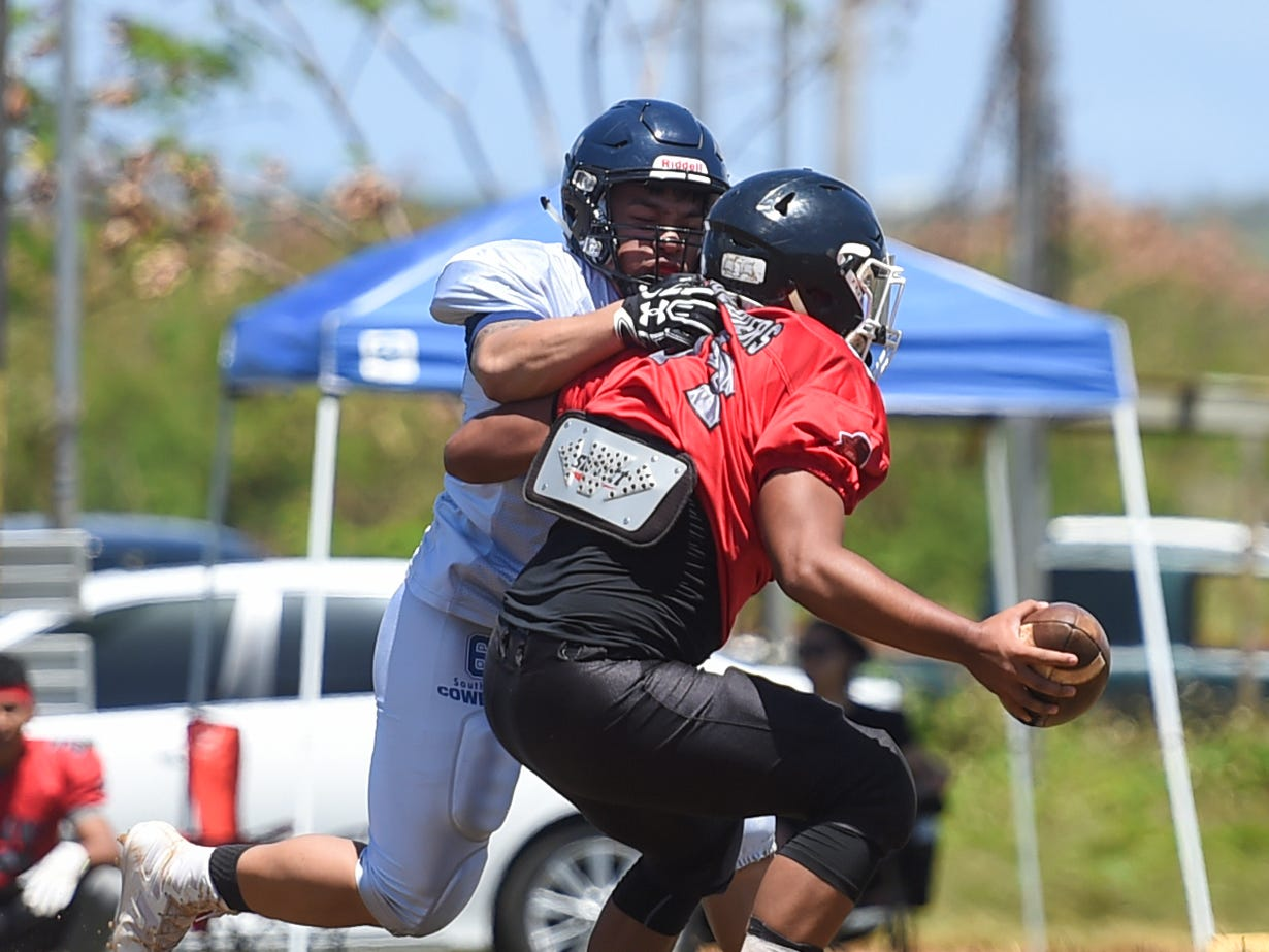 The Southern Cowboys' PJ Flores goes for a sack on Outlaws quarterback Kobe Quiambao during a Budweiser Guahan Varsity Football League game at Eagles Field in Mangilao, March 9, 2019.
