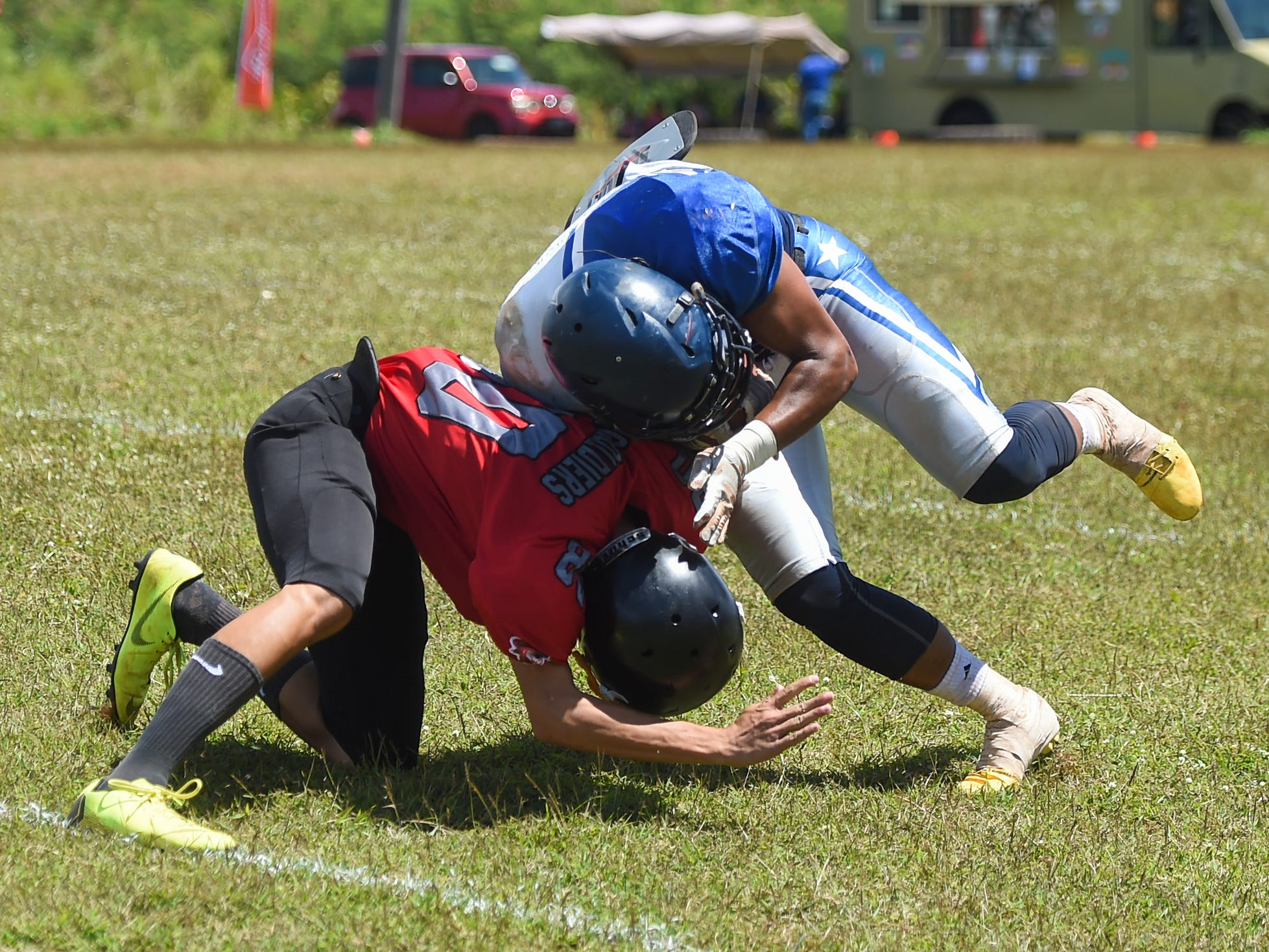 The Southern Cowboys' Connie Toney (1) clashes with an Outlaws player during a Budweiser Guahan Varsity Football League game at Eagles Field in Mangilao, March 9, 2019.