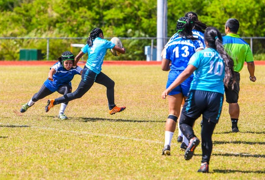 Southern High School Dolphins' Liz Quintanilla busts away from a tackle to score her first try during a Girls Varsity IIAAG/GRFU rugby matchup with Academy of Our Lady Guam Cougars on Ramsey Field at the John F. Kennedy High School in Tamuning on Saturday, March 9, 2019. In the end, the Dolphins swam away with the victory with a final score of 24-5.