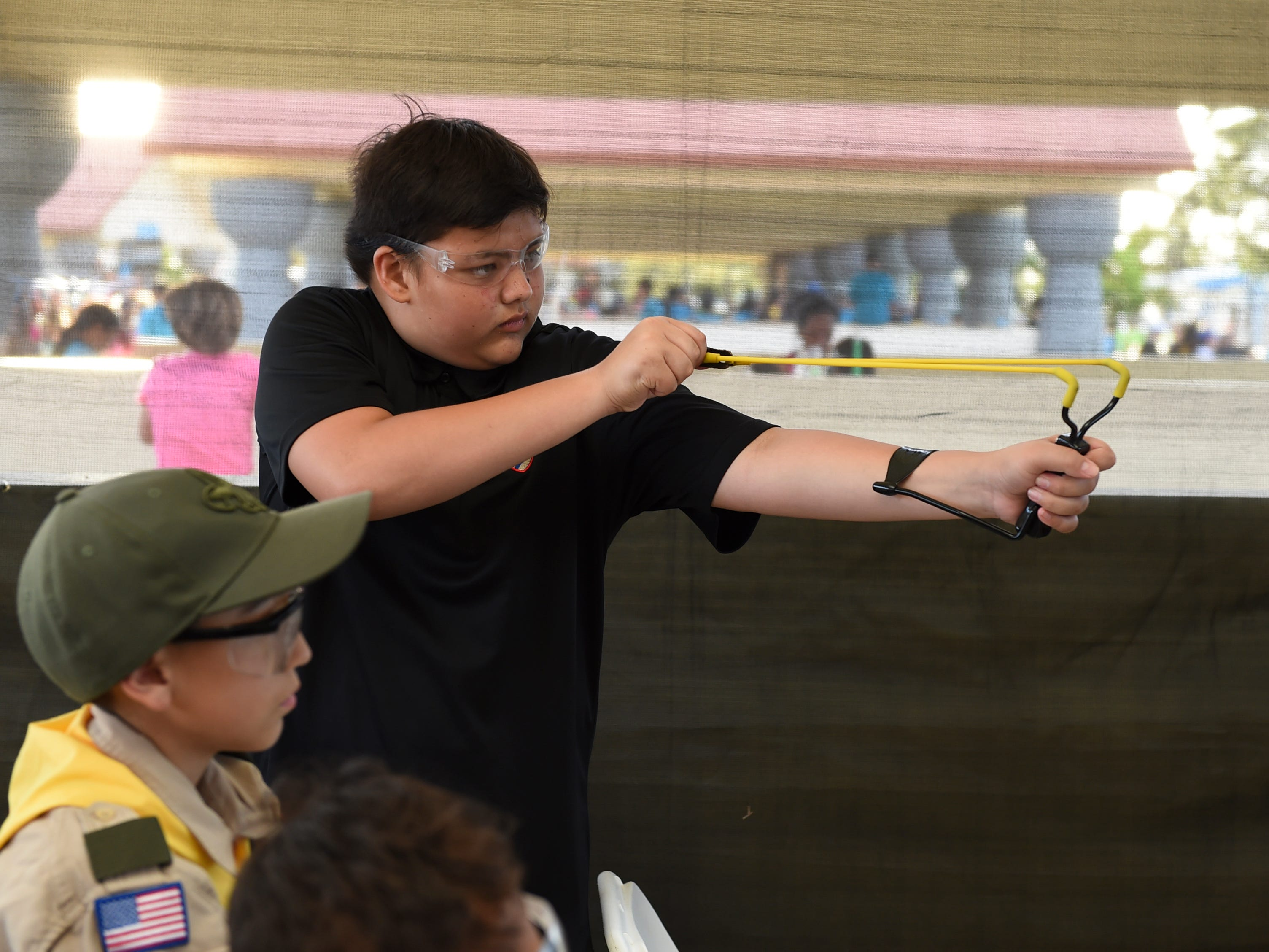 Issac Erickson, 13, shoots targets with a slingshot in the Boy Scouts of America Kid Zone booth during the Bank of Guam Ifit Run and Block Party at Chamorro Village in Hagåtña, March 9, 2019.