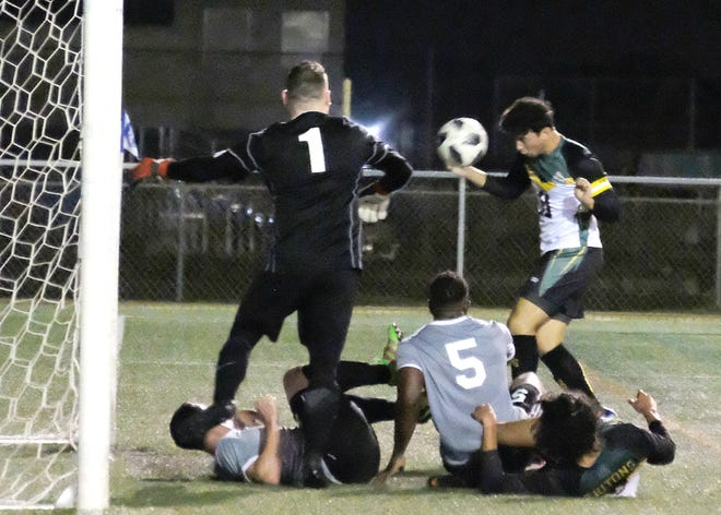 UOG's Dylan Naputi scores on a header against the GWM Bombers March 8, but the play is called back by off-sides. The Tritons won 6-3.